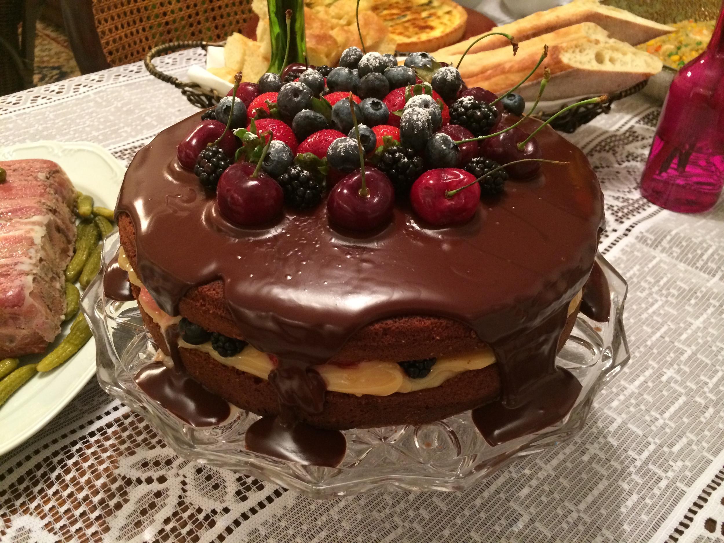 O bolo na mesa já preparada para receber os convidados.