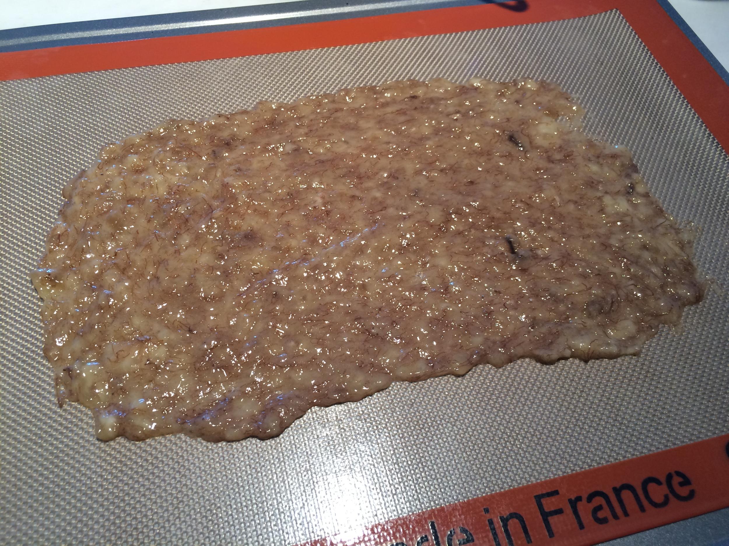 Amasse a banana com um garfo. Destrua qualquer grumo de banana que houver, tornando-a uma pasta lisa. Espalhe-a, com a ajuda de um pão-duro, em um tapete de silicone, até que fique com a espessura de 1 mm. Leve ao forno pré-aquecido a 80 graus Celsius e acompanhe de meia em meia hora. No meu forno, elétrico e muito preciso, levei pouco mais de 3 horas para conseguir o resultado desejado. Num forno à gás pode ser que este tempo seja maior.