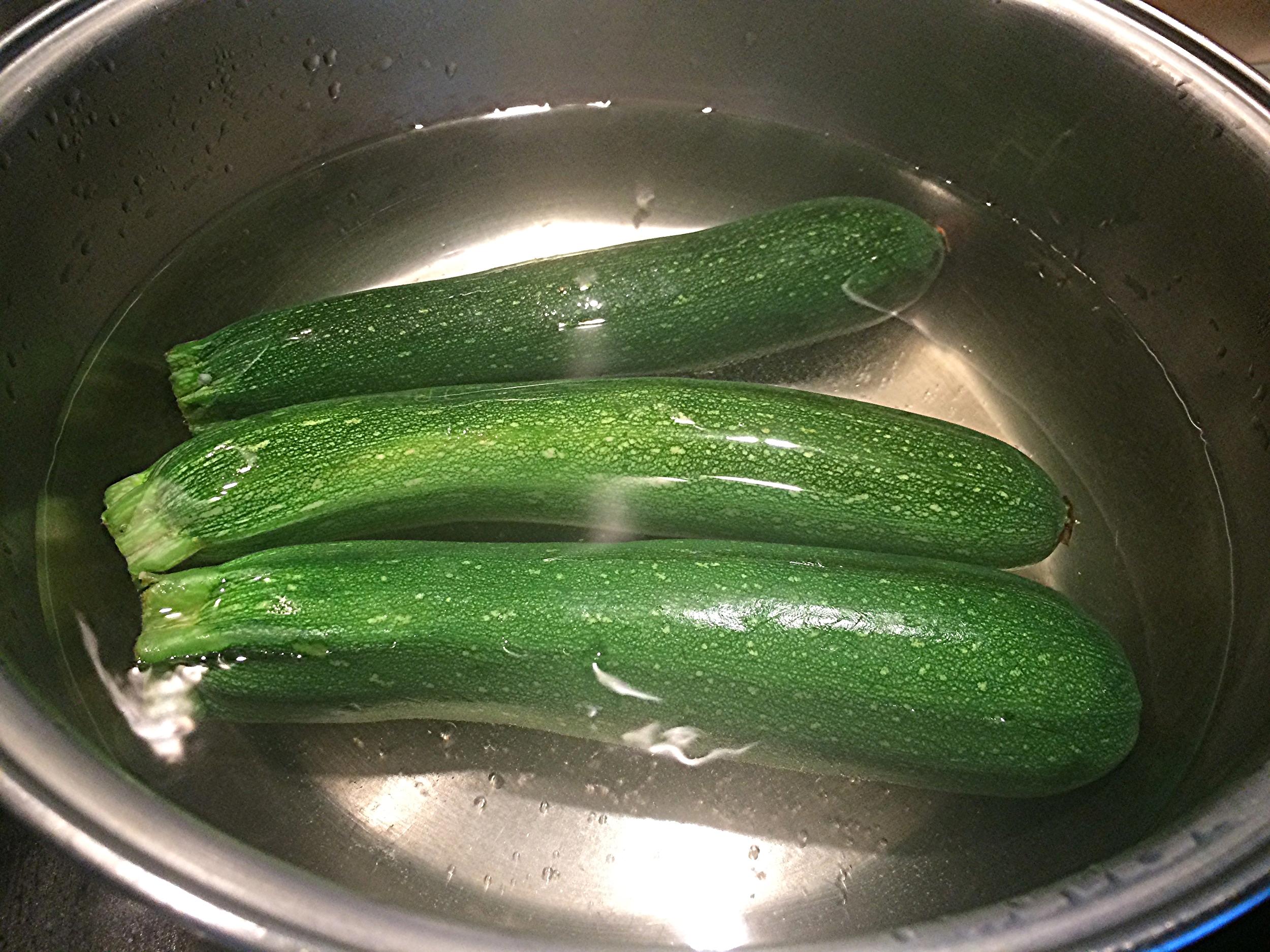 Enquanto a base do recheio esfria, coloque uma panela larga cheia de água no fogo. Junte uma colher de sopa cheia de sal refinado. Deixe a água entrar em ebulição e coloqueasabobrinhaslavadas, com cuidado. Deixe-as cozinhar. O ponto correto é quando vocêespeta uma faca nelas e elasse desprendem da faca rapidamente. Cuidado pra não cozinhar demais:as abobrinhas ainda irão ao forno! Uma vez prontas, retire-as do fogo, escorra a água quente e coloque-as em banho maria invertido, ou seja, de molho em água com gelo, até que esfriem por completo.