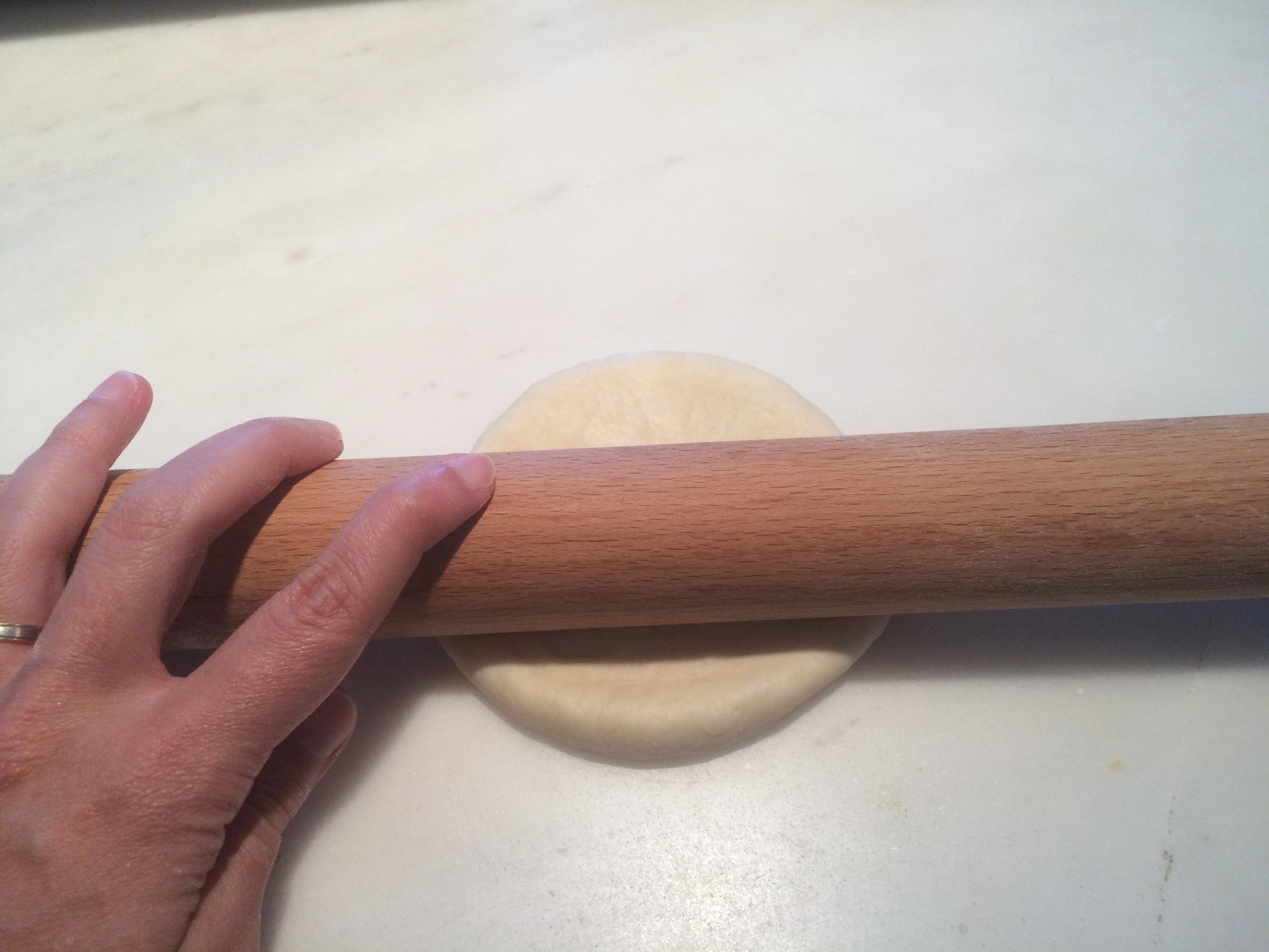 Com a ajuda de um rolo, abra a massa em formato oval para poder enrolar os pães.