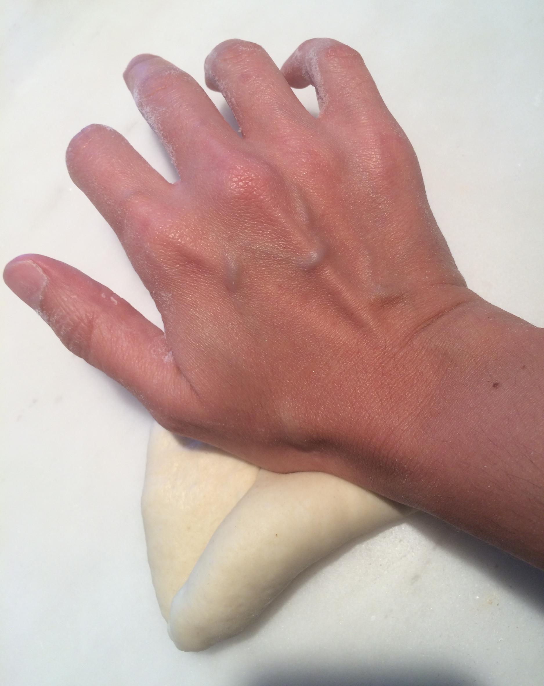 Enrole a massa sobre si mesma aos poucos, apertando cada volta com a base da mão, para que o miolo fique bem fechadinho. Ao terminar de enrolar, belisque as bordas para emendar o pão direitinho, pra ele não correr o risco de abrir enquanto estiver crescendo ou assando.