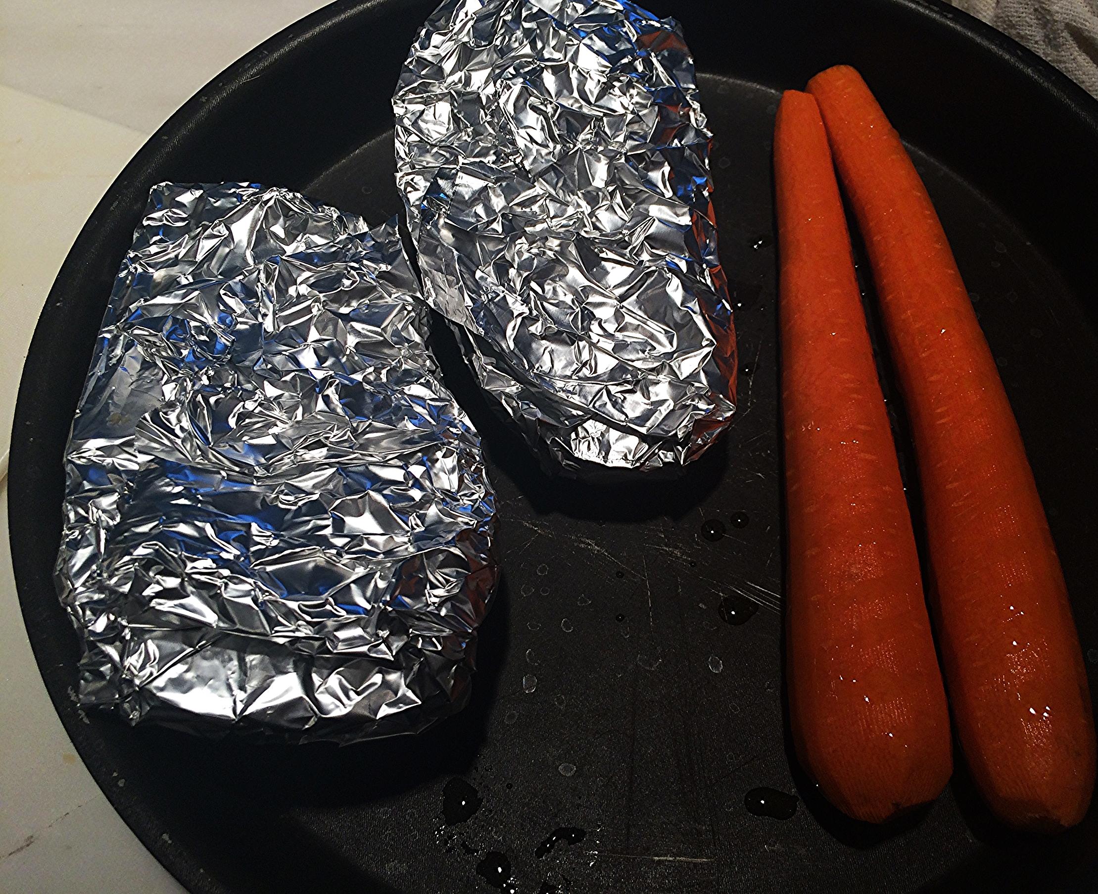 Embrulhe cada metade da berinjela no papel alumínio e coloque numa assadeira. Aproveitei e coloquei as cenouras junto porque tinha bastante espaço. Leve-as ao forno até que ao espetar uma faca na parte mais grossa da cenoura, ela solte imediatamente. O ponto da berinjela é quando ela estiver transparente e muito macia. Retire do forno. Reserve as cenouras para esfriarem. Abra os pacotes de berinjela e raspe a polpa, com a ajuda de uma colher de sobremesa, deixando só a casca pra trás. Reserve e deixe esfriar.