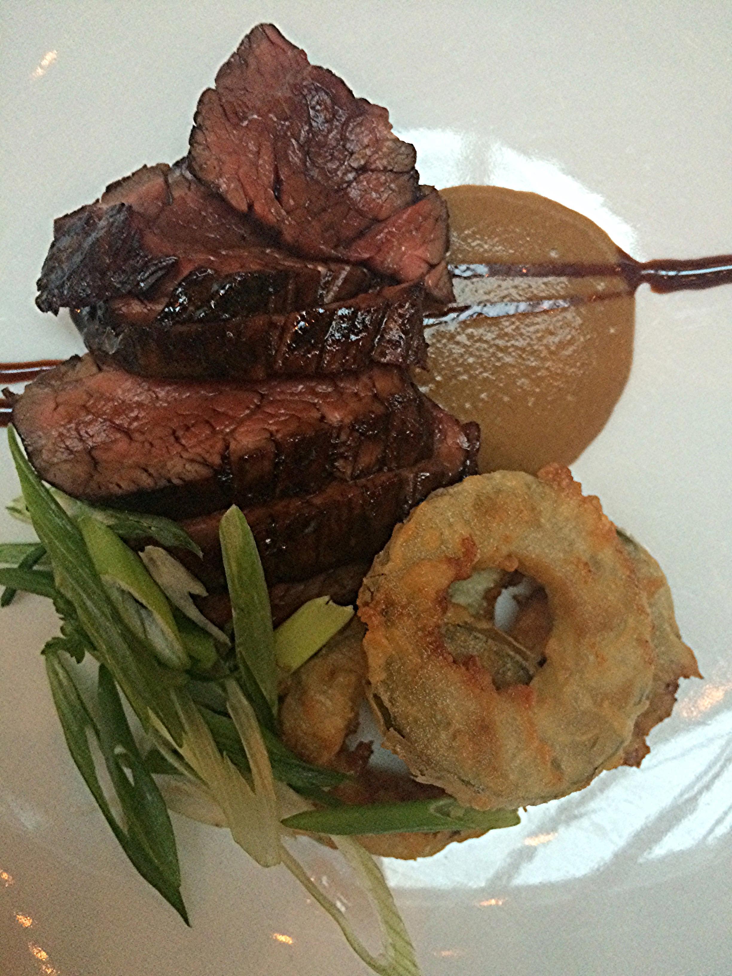 Um Hanger Steak grelhado (um corte na região peitoral do gado),Mostarda japonesa, molho de uma espécie de enguia e cebolinhas.