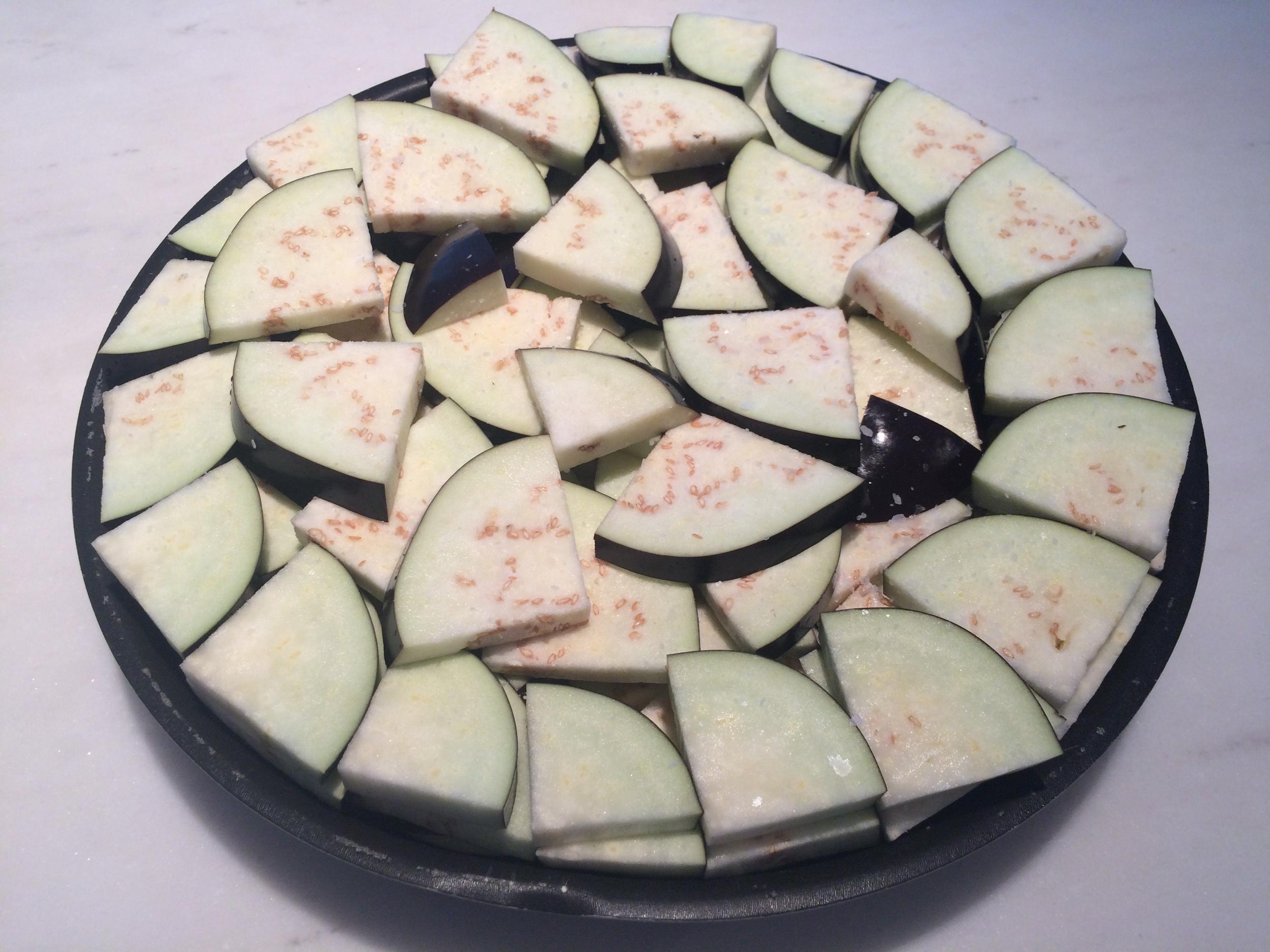 Pique-as em fatias e depois as fatias em quadrantes. Disponha-as em camadas numa assadeira, tomando o cuidado de polvilhar sal por cima de cada camada.