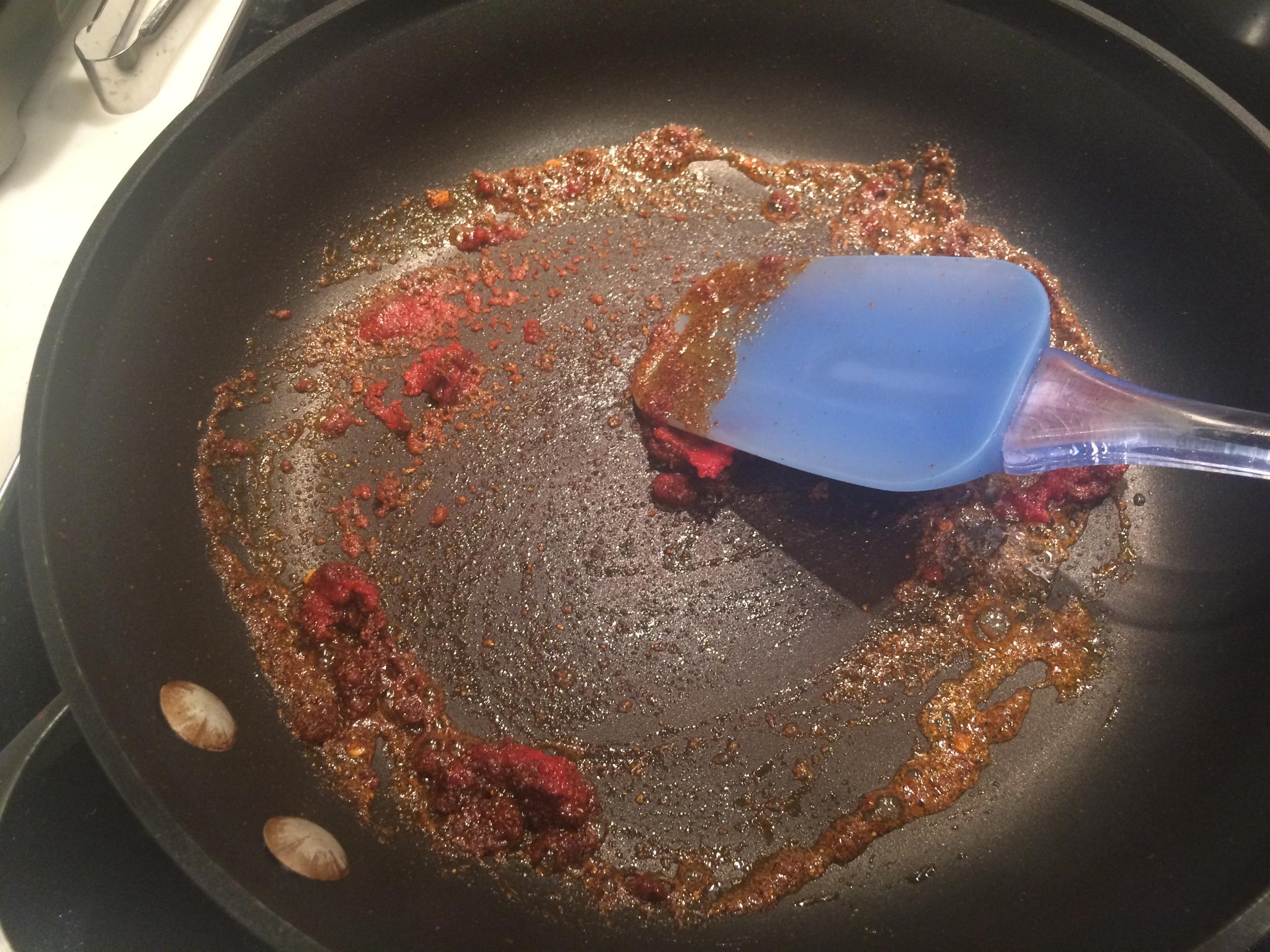 Aqueça a panela em fogo médio. Coloque o azeite, o harissa, o extrato de tomates, o alho, o cominho e metade do sal. Misture de modo que a mistura aqueça por igual e libere seu perfume.