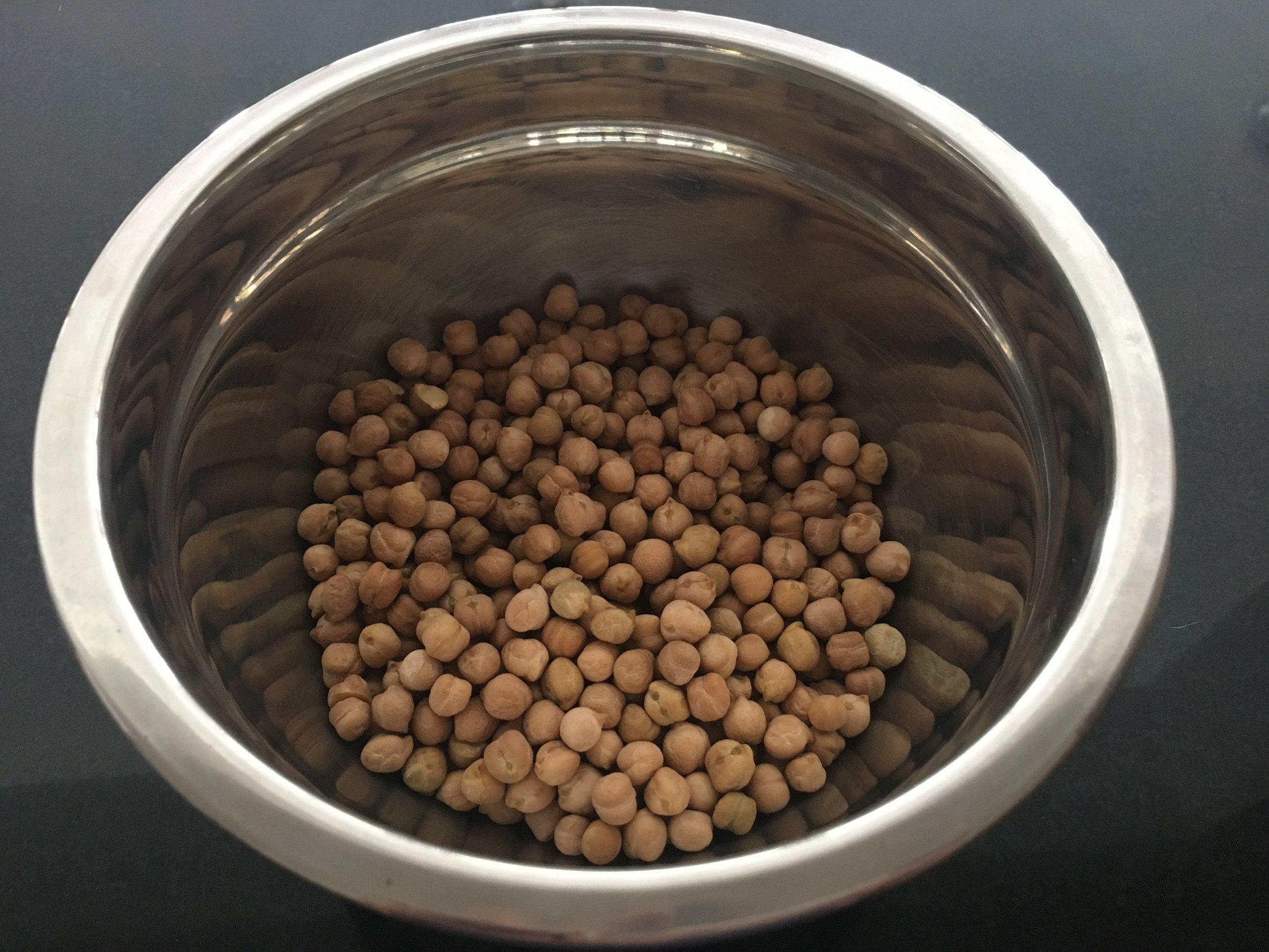 Ponha o grão de bico de molho por 12 até 24 horas. Os grãos irão mais do que dobrar de volume, portando coloque 3 vezes mais água que as medidas de grãos. Cubra e leve a vasilha à geladeira.