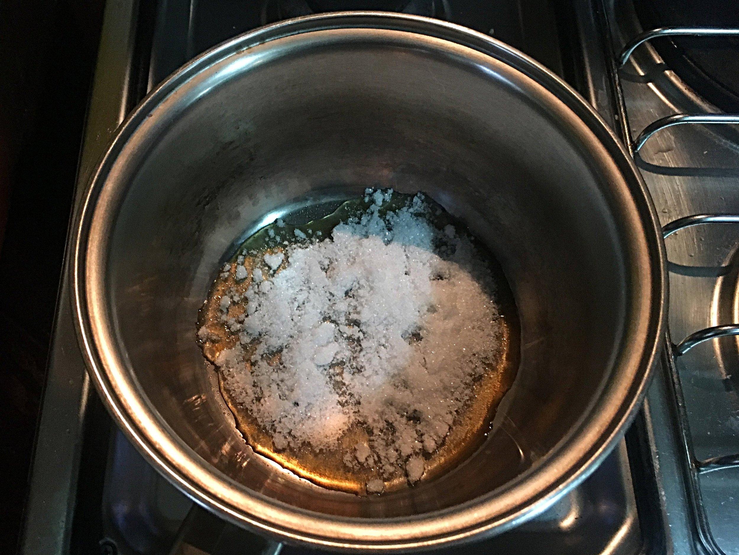 Numa panela, leve ao fogo o açúcar 1 e deixe derreter, mexendo com um garfo pra desfazer os grumos. É importante cuidar que o açúcar não escureça nesta etapa onde ainda há uma parte sem derreter. Use o garfo pra misturar os grânulos de açúcar com o caramelo que vai se formar nas laterais.