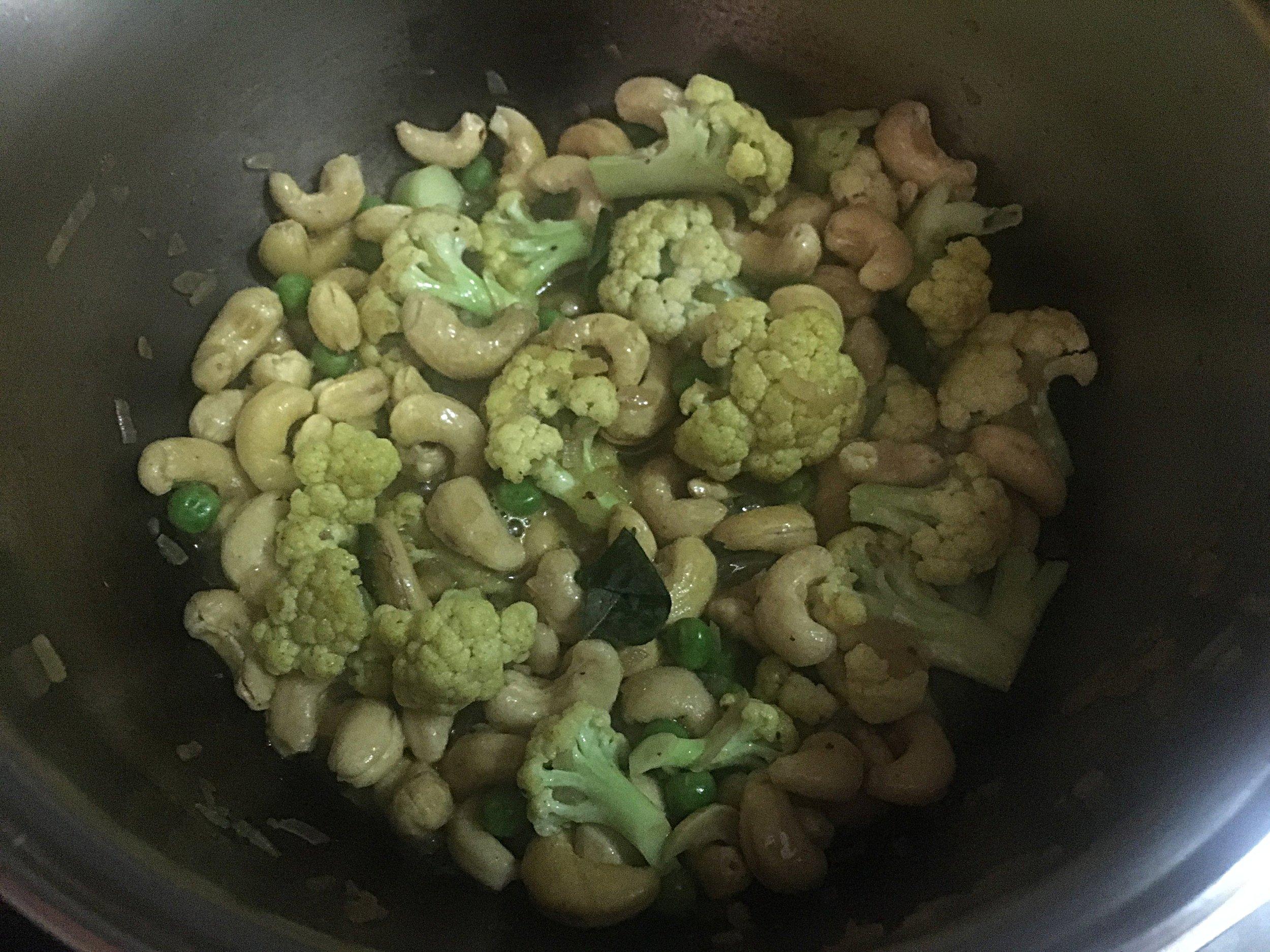 Adicione o  curry  e mexa, aguardando para o que pó se dissolva e comece a liberar aroma. Adicione o restante da água e deixe levantar fervura. Coloque as ervilhas e o leite de côco e deixe ferver em fogo baixo, panela tampada,por 5 minutos.