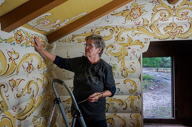 @salliedereus studies the original #Rosemåling design by the late Norwegian painter Sigmund Aarseth along the walls of @Binkhaven in #DoorCounty, Wisconsin. Once an apprentice of Sigmund herself, Sally continues the work onto the ceiling to match his unique 70's style using a dry brush technique in a modern telemark style. #ScandinavianAmerican