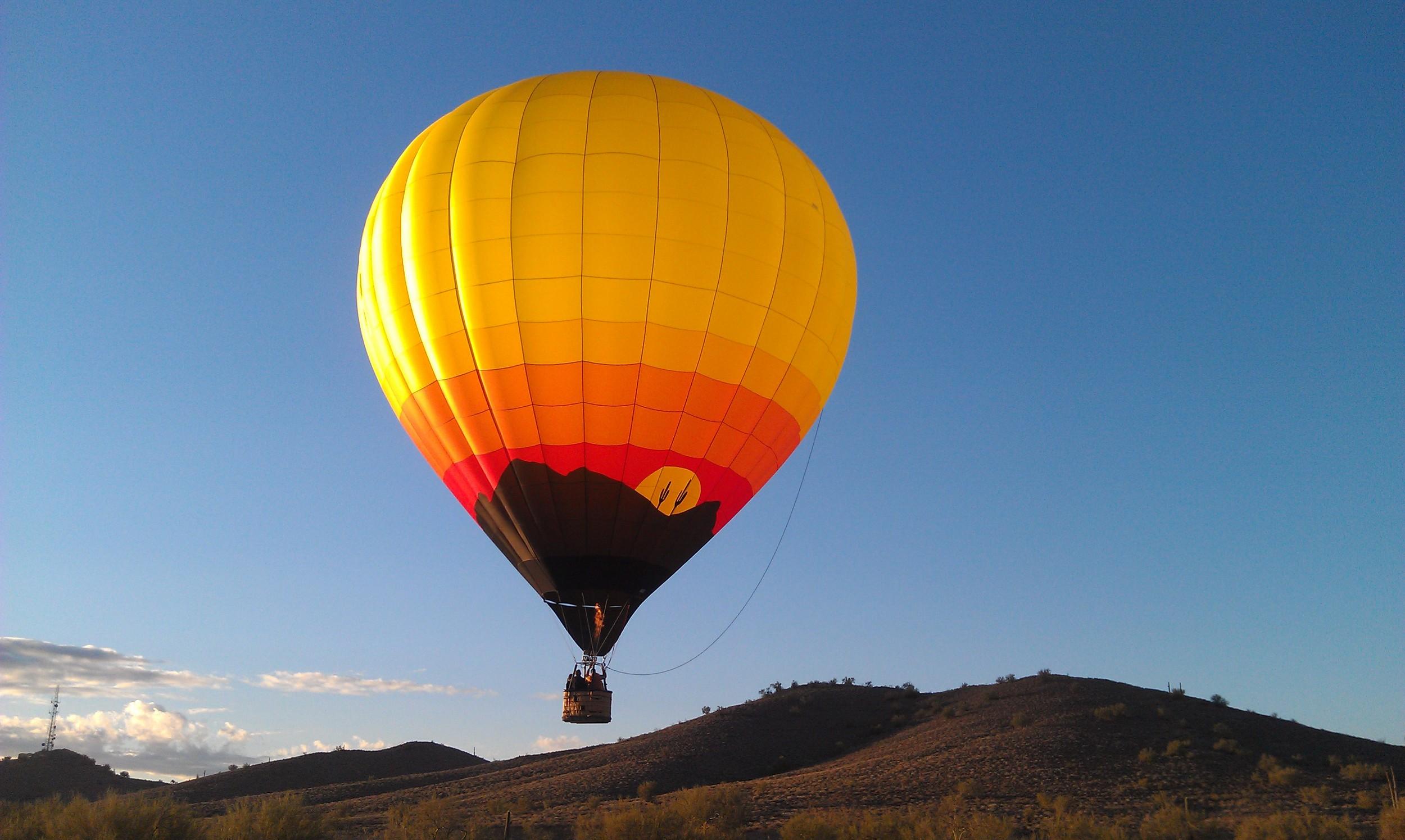 A hot air balloon flight nearing it's landing spot.
