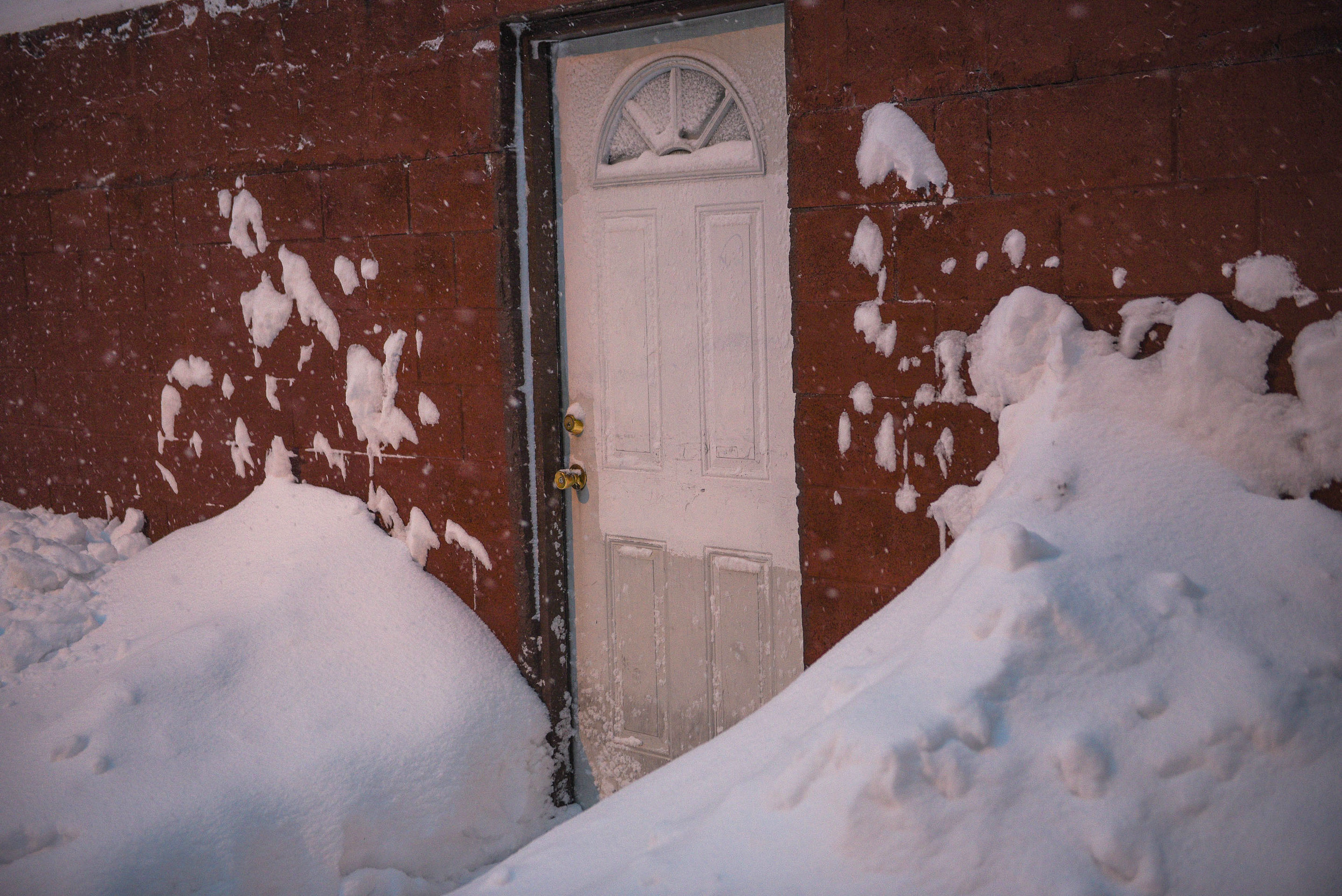 Mountains of snow by a doorway.