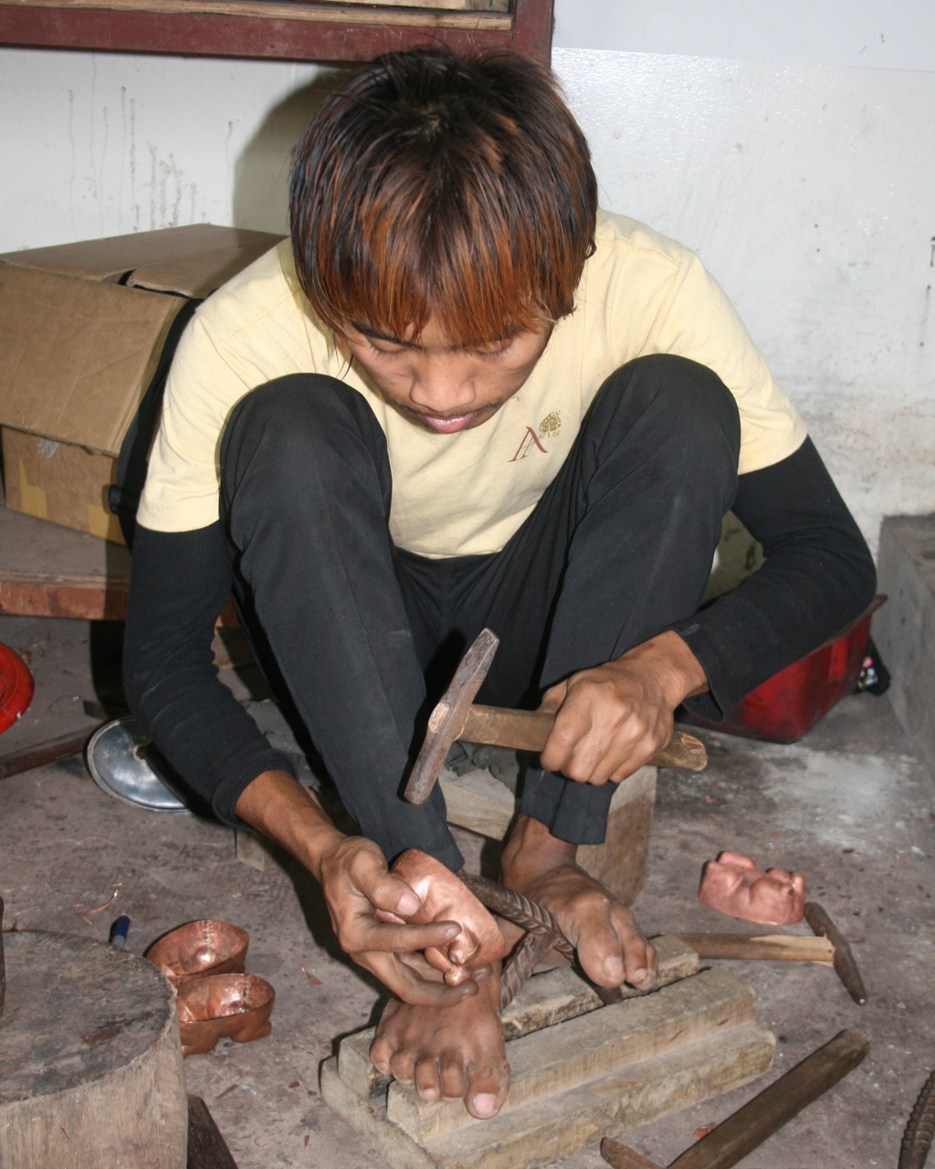 Cambodian artist Panya crafts copper animal betel boxes at his shop in Siem Reap.