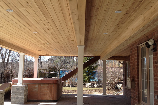 The beautiful underside of a large deck.  A shady area, well lit for evenings outdoors.