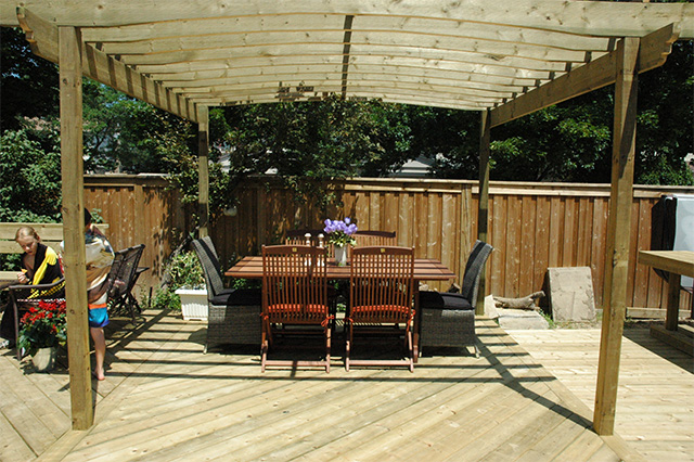 This backyard oasis is a deck with trellis and seating, ready for a party.