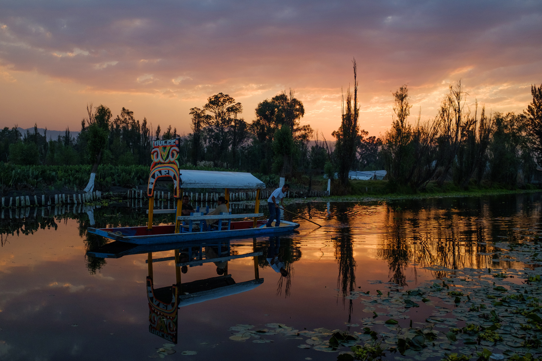 March 3, 2018 - Mexico City, Mexico: A trajinera floats by at sunset in Xochimilco. (GOOD Magazine/Mallika Vora)