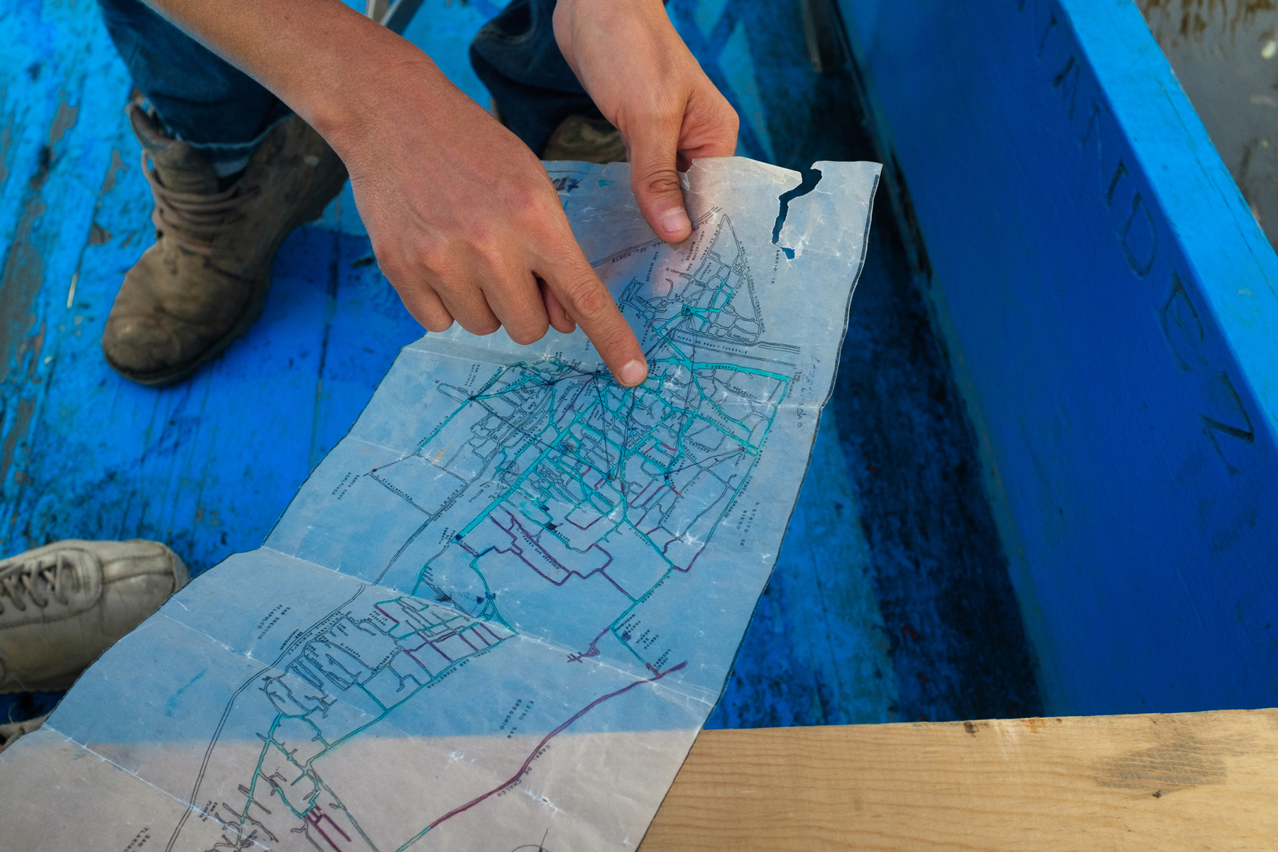 March 3, 2018 - Mexico City, Mexico: Carlos Maravilla Santos, co-founder of Plan Acalli, traces currently passable routes on an intricate map of the canals of Xochimilco. (GOOD Magazine/Mallika Vora). (GOOD Magazine/Mallika Vora)