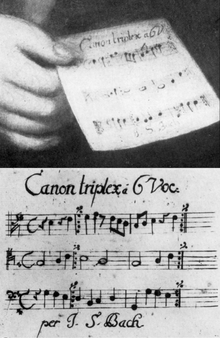J.S. Bach, Canon triplex a 6 vocibus (canon for six voices)was presented as his 'entrance work' to Mizler's Societät and is also the one that he holds in the Haussmann portrait.