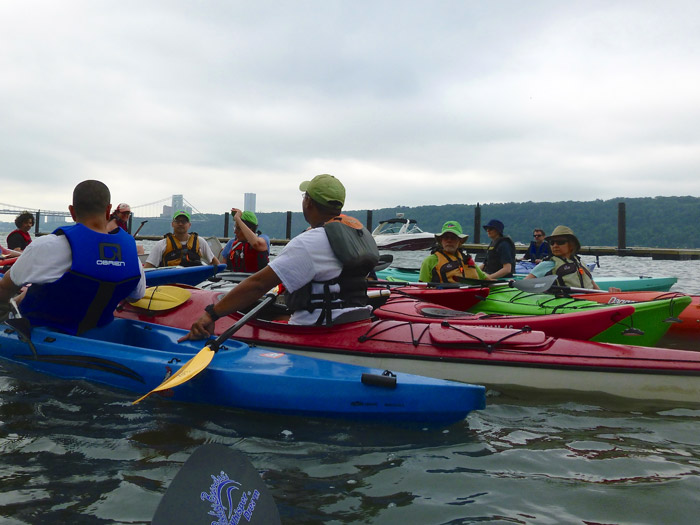 Gathering for a pre-paddle talk on the water.