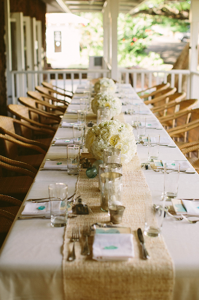 Burlap Table Runner Spotted with Elegant White Flower Arrangements