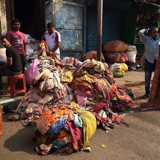 Sorting saris on the road for sale and recycling