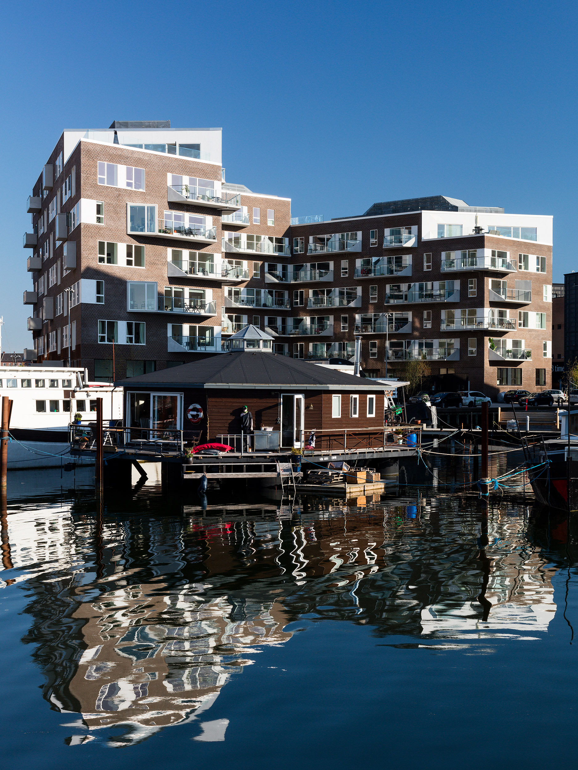 Residential housing, Skibbroen, realised by Holscher Nordberg Architects. Photographed from early morning throughout the day, letting the sun emphasise the various aspects of the buildings character.The special life that characterizes Skibbroen occurs due to users' various activities and the mix of tranquility, activity, transit and practical doings.The uniqueness of the channel and harbor space is maintained. Photographed from early morning throughout the day, letting the sun emphasise the various aspects of the buildings character.