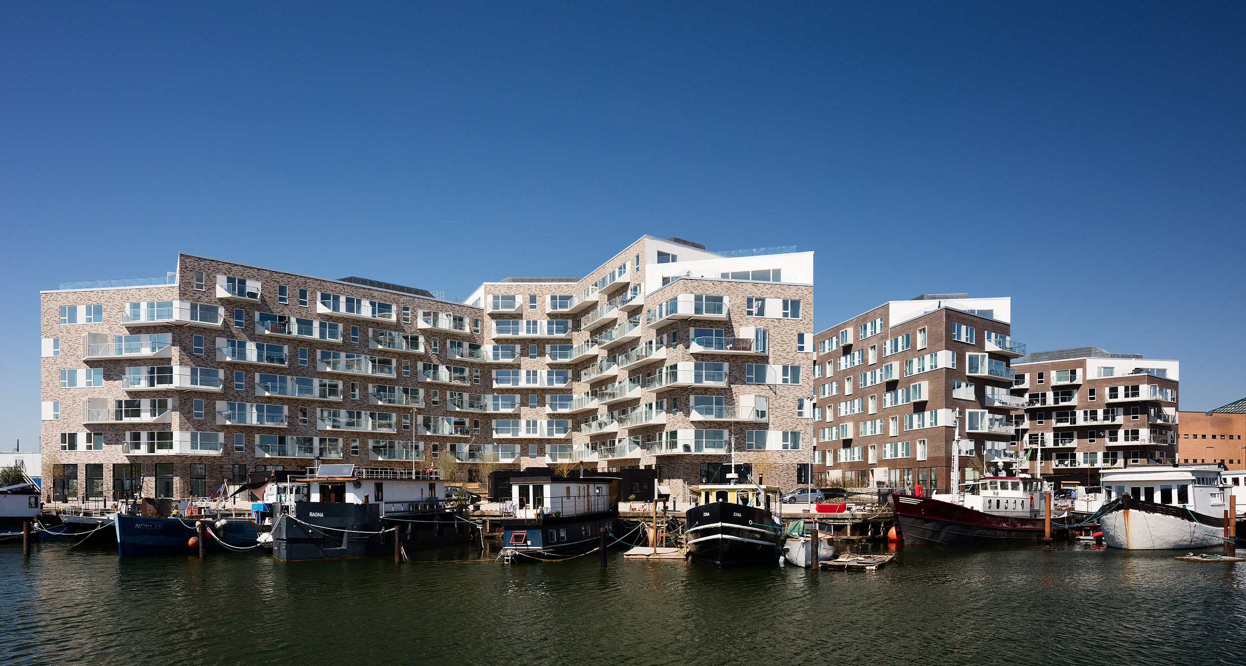 Residential housing, Skibbroen, realised by Holscher Nordberg Architects. Photographed from early morning throughout the day, letting the sun emphasise the various aspects of the buildings character. The special life that characterizes Skibbroen occurs due to users' various activities and the mix of tranquility, activity, transit and practical doings.The uniqueness of the channel and harbor space is maintained. Photographed from early morning throughout the day, letting the sun emphasise the various aspects of the buildings character.