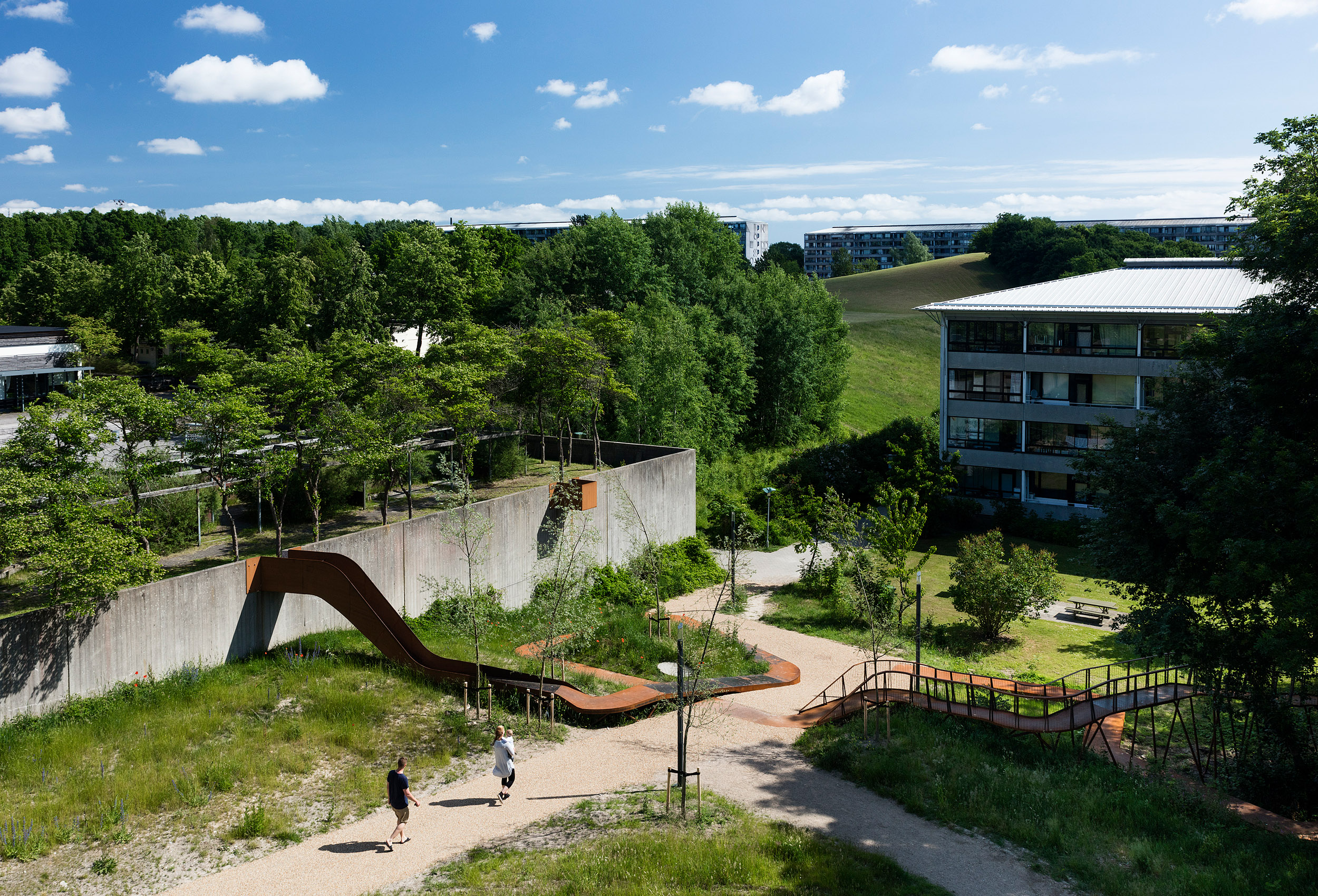 The Loop, realised by Holscher Nordberg Architects  Værebro Park, a residential area in the suburbs of Copenhagen, has in the last years suffered from high crime rates and a declining number of inhabitants. Placed in the intersection between an indoor swimming pool, a primary and secondary school, and the 1400 dwellings of Værebro Park, the activity path aims to create a physical and mental bridge between the different users of the area. The low budget yet esthetical element is designed as a playful path offering a variation of activities.