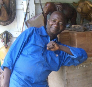 Divine, an artist in Ghana, is posed with awooden chest, beforehe carved itfor The Yonkofa Project.To the left,is a picture of the completed chest, whichwill be available at our event, Sept. 13, 2014.