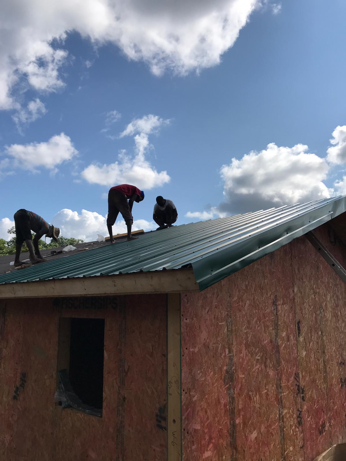 Putting on the metal roofing.