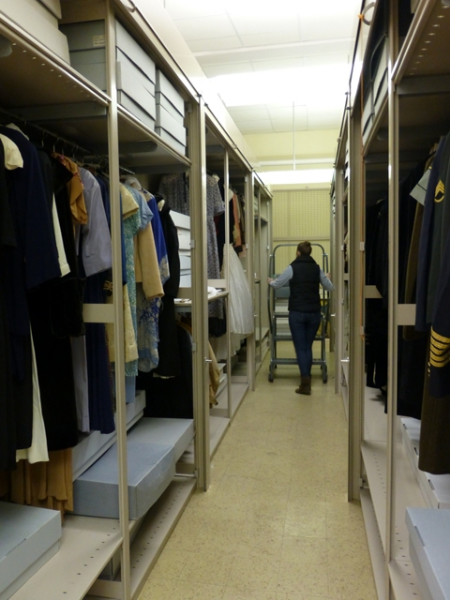 Intern and UW-L student Callie O'Connor in the hanging costume storage.