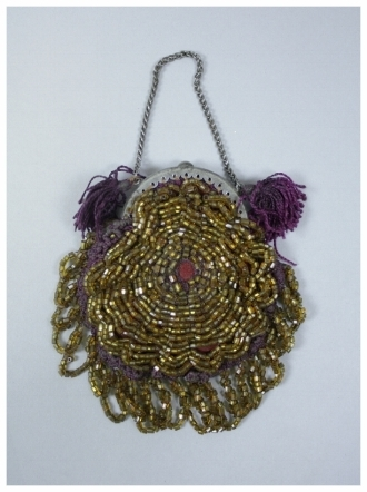 c. 1860  A light brown beaded purse with crocheted purple backing and purple tassels. Silver metal frame and interlinked chain for carrying. There is a row of beaded brown looped fringe along the bottom. The purse is most likely handmade.