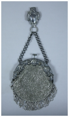 """c. 1880  A metal beaded chatelaine purse that is round in shape with tassels on bottom. It has a metal frame with contains 3 cherubs an ornate design. The back of bag is suede and not beaded. Has chain extending from outside of frame on top which connects to an ornate belt clip. There was a note found inside bag with text """"Grandma Halughorst bag to be worn on the belt. She made it herself."""""""