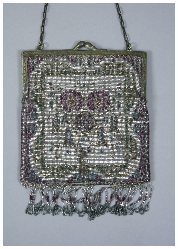 A beaded purse made in Germany with tiny metal metallic beads in floral and geometric patterns. Bead colors include:silver, green, gold, purple, and blue. Purse has gray faille lining. Gold metal frame and clasp with interlocking chain. Fringe looping on the bottom of silver, purple, gold, and green.