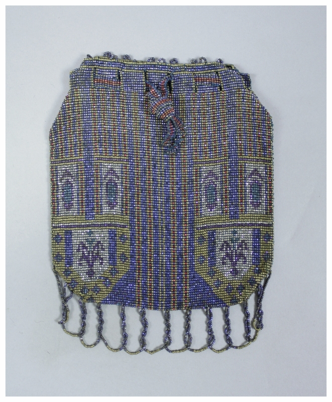 A beaded bag with a geometric design in blue, gold, red, purple, and silver. The beads are woven into the design.There is beaded fringe along the bottom. The drawstring is made of beads.
