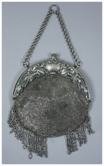 """c. 1900  A beaded purse. It has a leather back and steel cut beads going around in a circular pattern. There is an ornate """"German Silver"""" frame and a chain. The purse has beaded fringe hanging off the bottom. The beads are notably rusted."""
