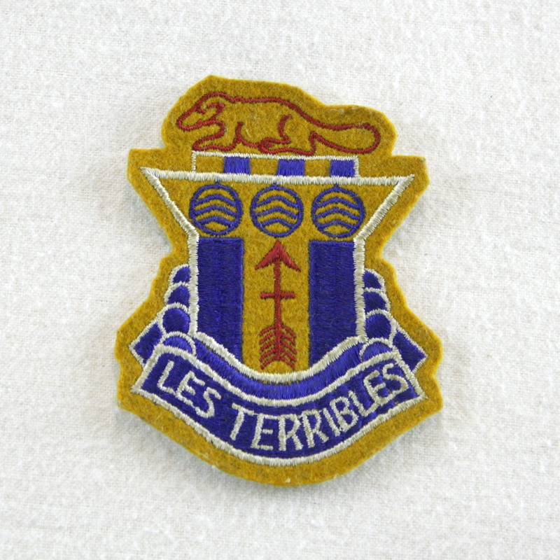 """The U.S. 32nd Infantry Division was formed from Army National Guard units from Wisconsin and Michigan and fought primarily during World War I and II, the red line through a red arrow signified the tenacity of the 32nd in breaching enemy lines, the stiching on the badge """"LES TERRIBLES"""" refers to the nickname given to the division while fighting in France during WWI."""