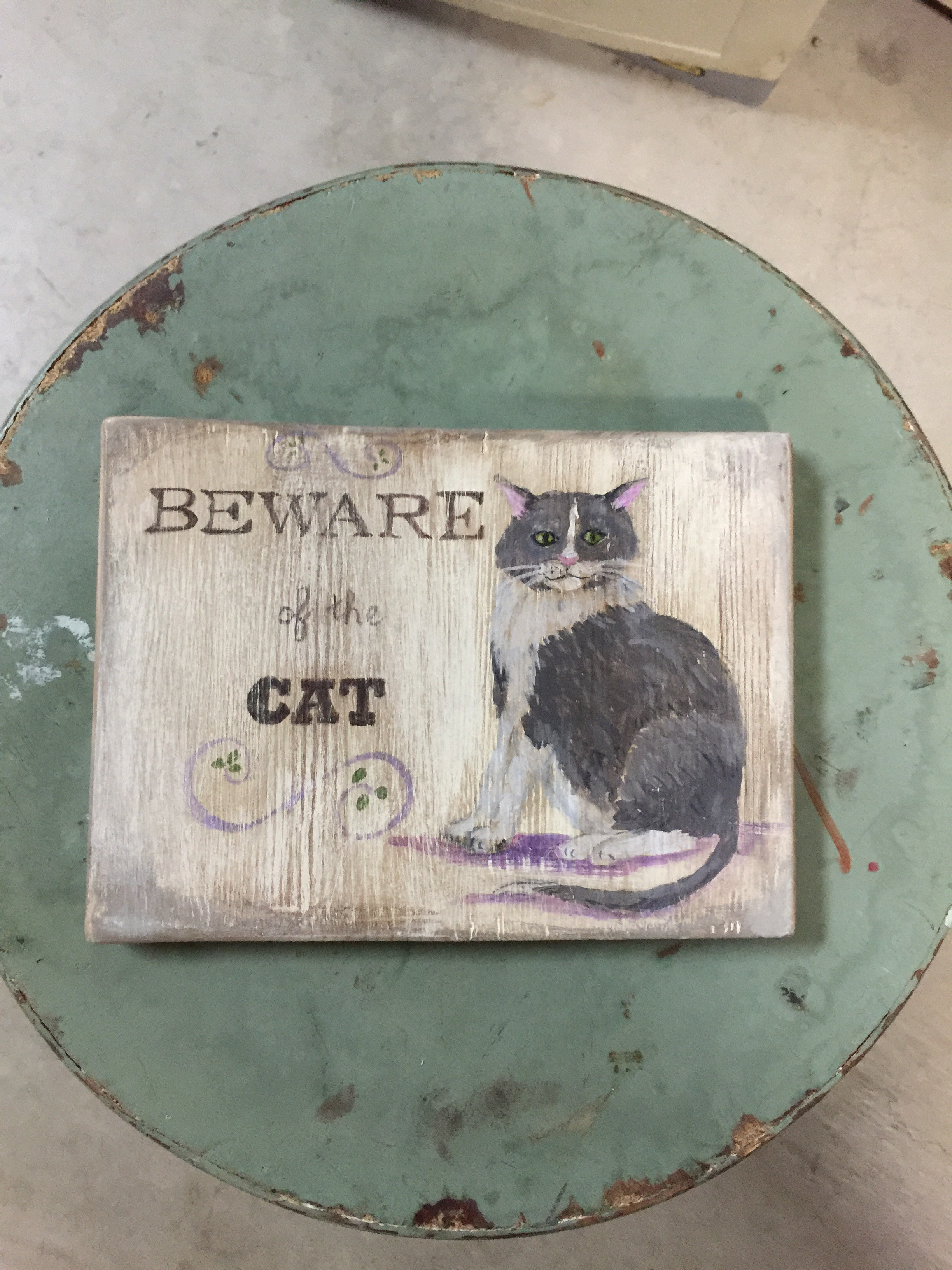 Hand painted cat beware sign on fence wood.