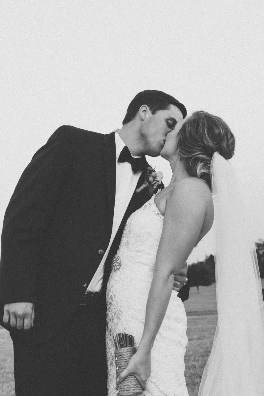 bride and groom kiss film black and white film