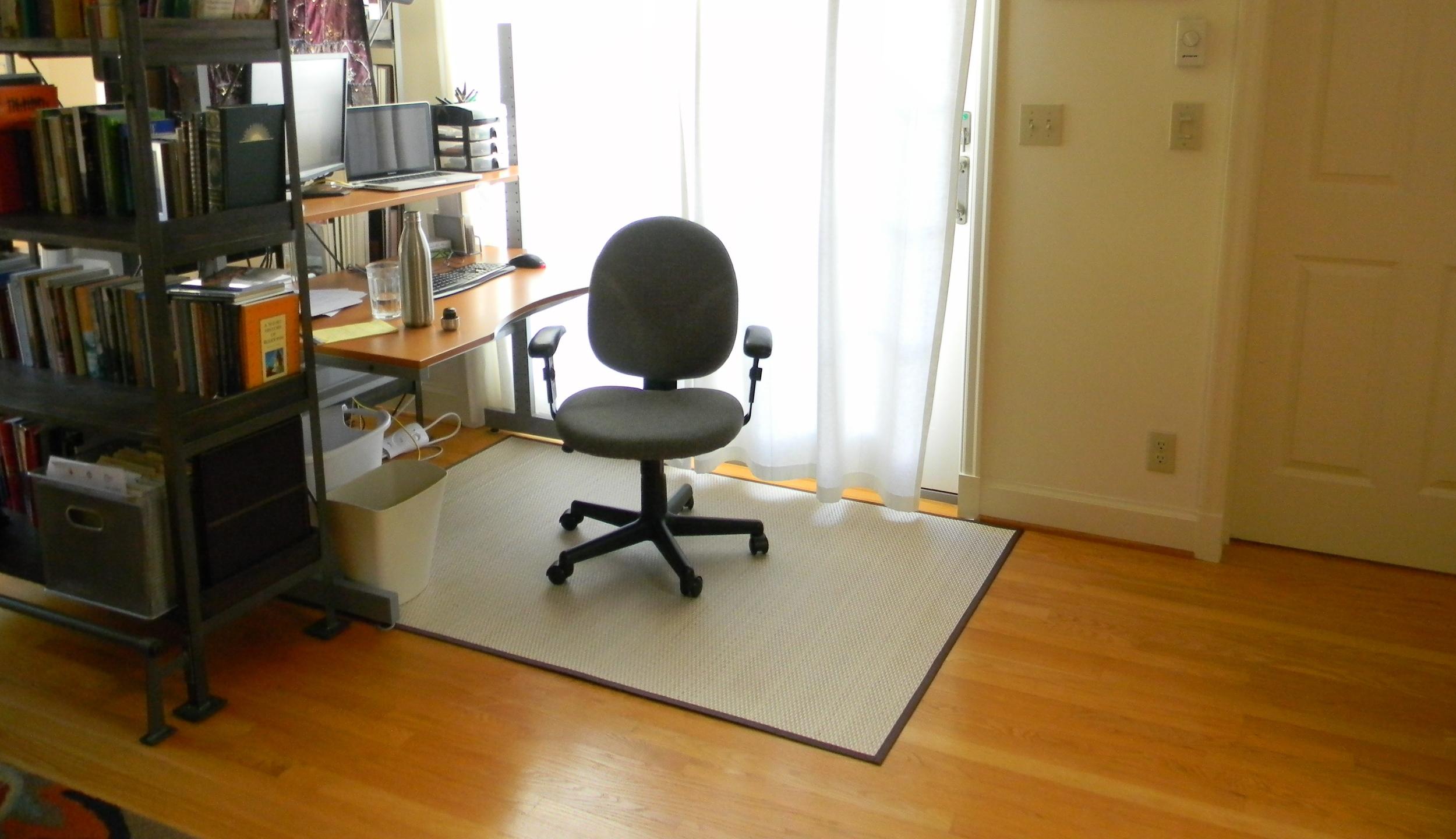 Room-dividing bookshelves, put into an L-shape, making a nook for a desk on one side...