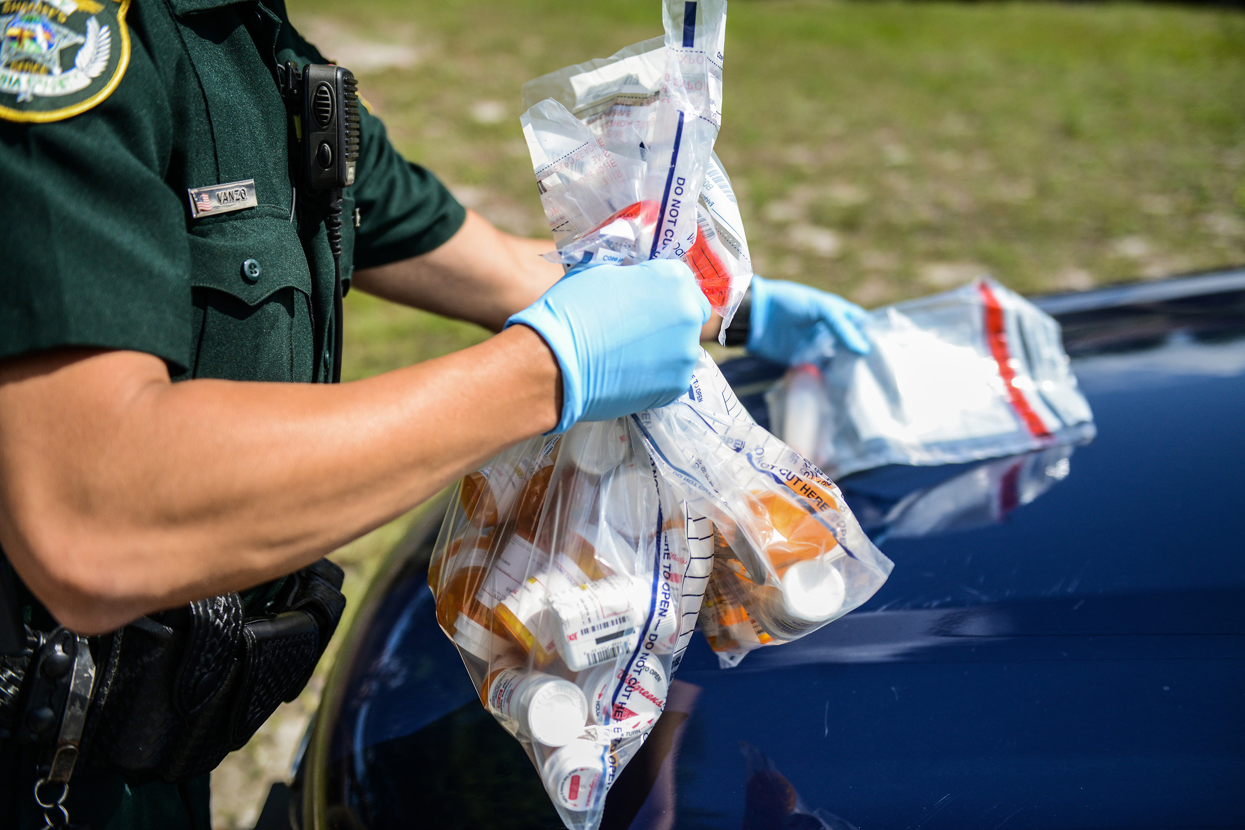 Volusia County sheriff's deputy Michael Vanzo holds five bags of medication and drug paraphernalia removed from Joshua Lacy's home. Investigators believe Lacy died after injecting heroin. Deltona on Friday, April 13, 2018.
