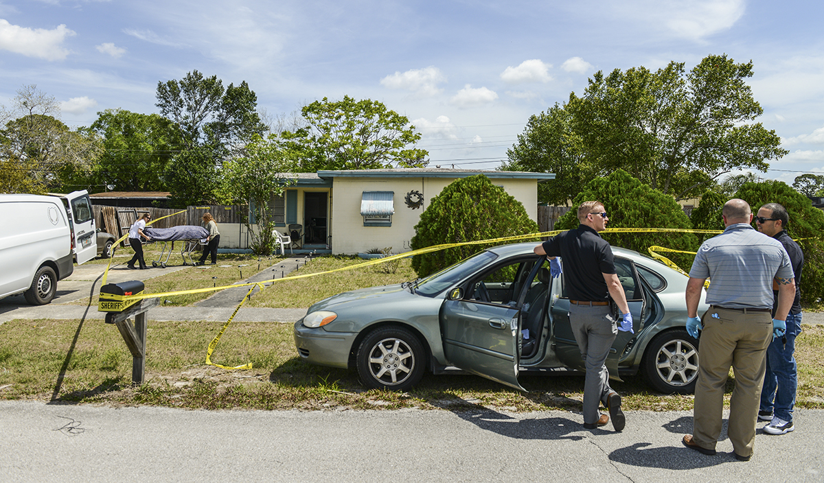 Volusia County Sheriff's Office detectives Jarett Wooleyhan, Shon McGuire and Miguel Roman prepare to search the vehicle of a woman, Jenna Miller, believed to have died of a heroin overdose. In the background, medical examiners remove Miller's body from a Deltona home. Miller's 20-month-old son was in bed with her when she died. Deltona on Friday, March 30, 2018.