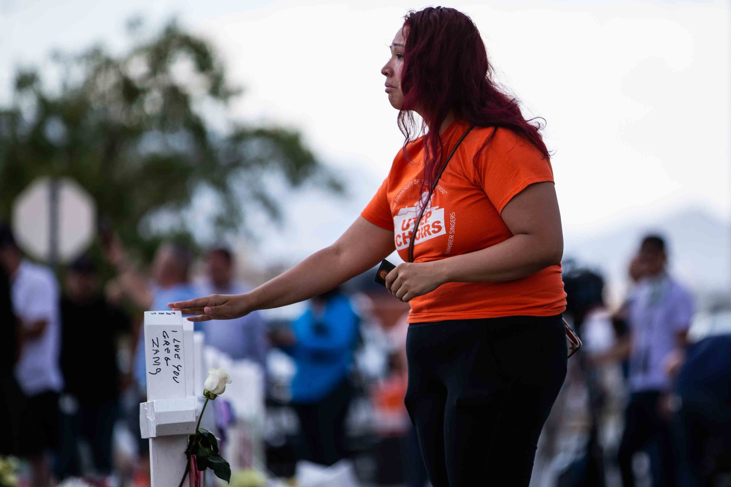 A woman approaches the crosses with the names of the victims of the mass shooting occurred in Walmart last Saturday morning have been placed on the scene to honor their memory in El Paso on Monday, August 5, 2019.