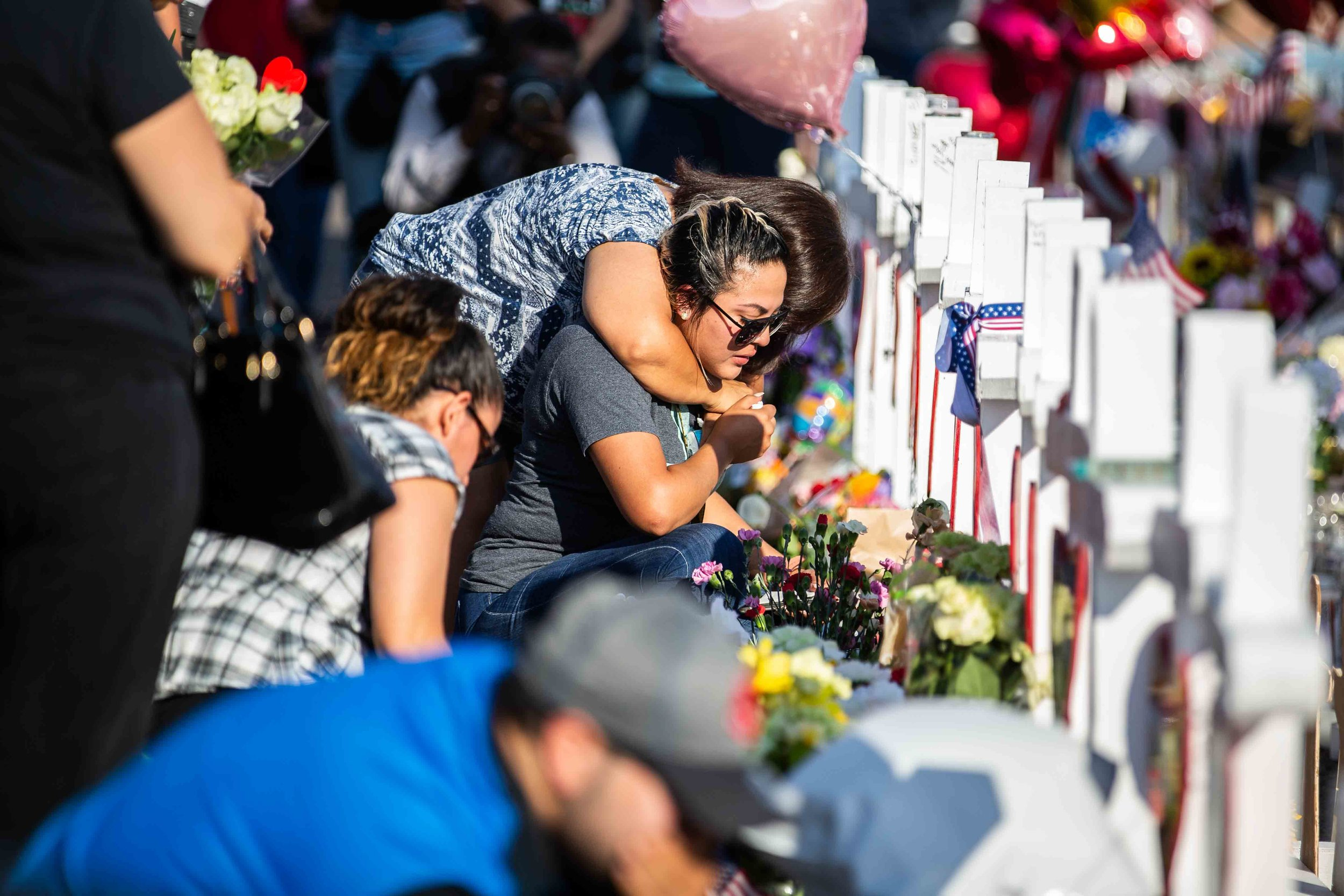 Pleople gather near the scene where crosses with the names of the victims of the mass shooting occurred in Walmart last Saturday morning have been placed to honor their memory in El Paso on Monday, August 5, 2019.