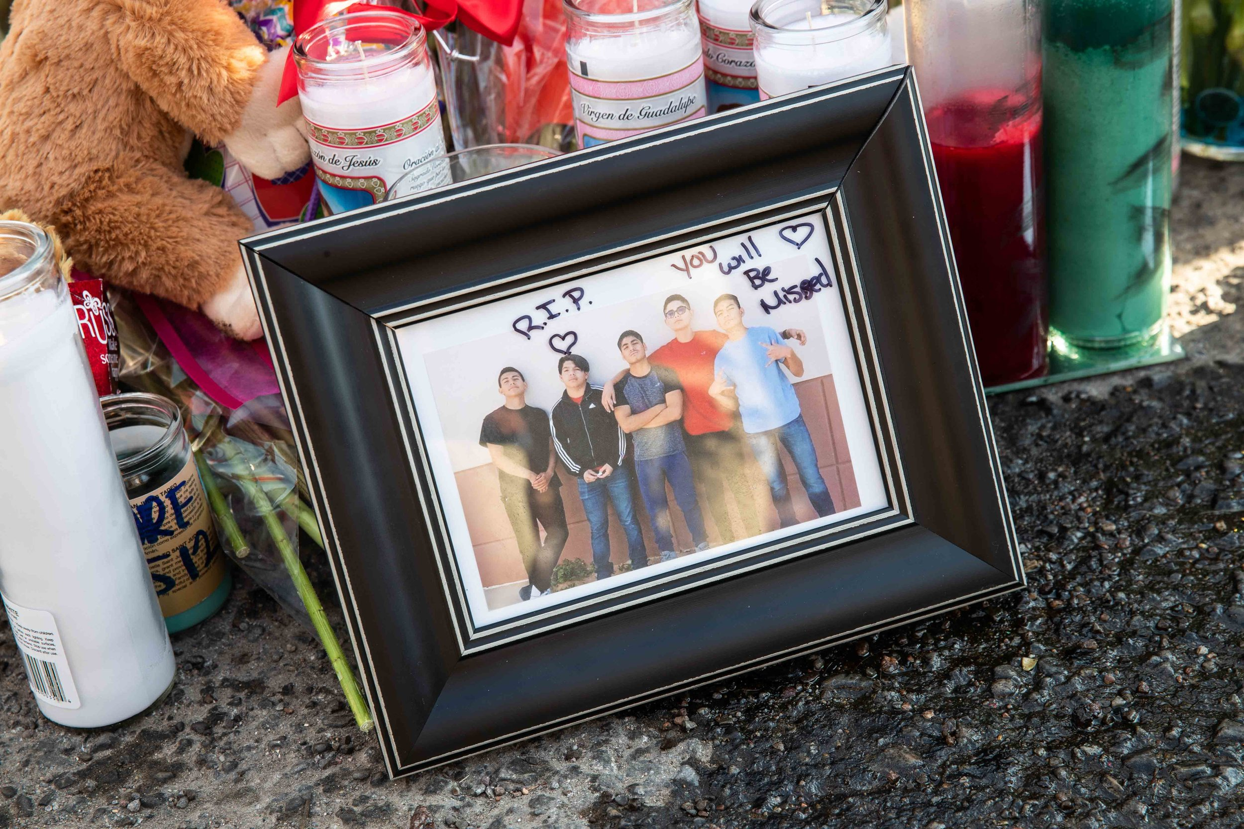 A photo of Javier Rodriguez posing with his friends is placed on the scene to honor his memory in El Paso on Monday, August 5, 2019.