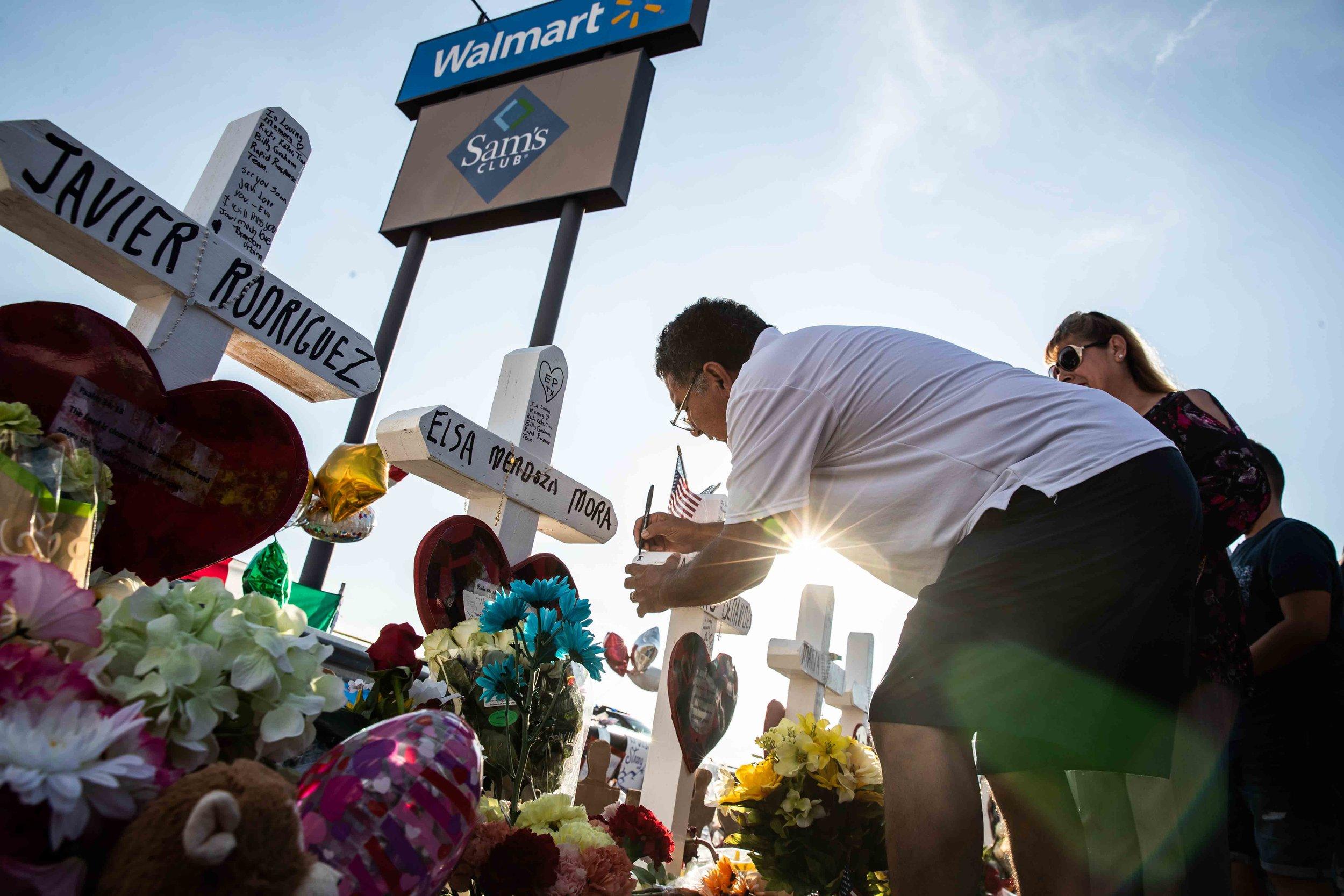 Armando Moreno next to his wife Martha Moreno, writes a message on Arturo Benavides' cross to honor his memory in El Paso on Monday, August 5, 2019.