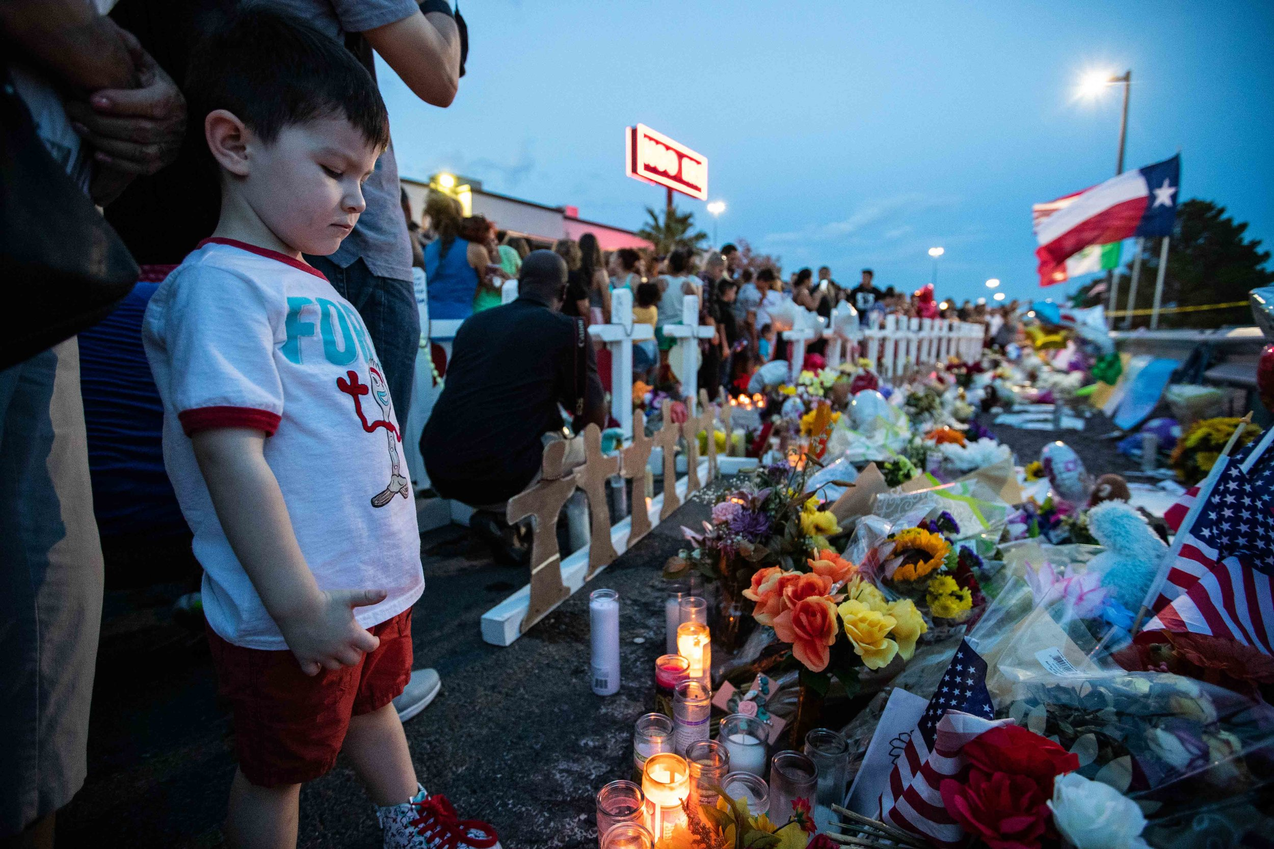 Roy Cedillo, 4, looks at some of the candles, flowers and flags that were placed on the scene to honor the victims of a mass shooting occurred in Walmart las Saturday morning in El Paso on Monday, August 5, 2019.