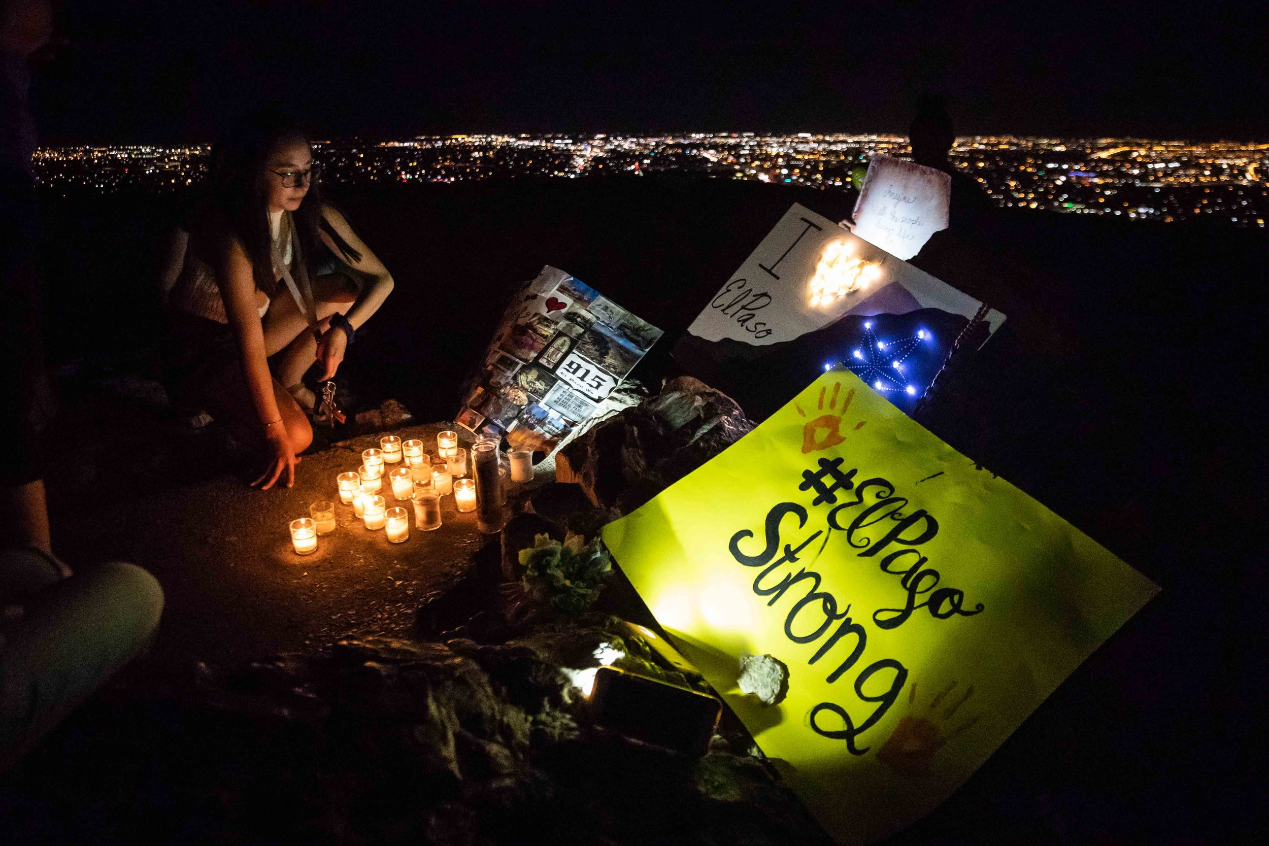 Chloe Trujillo sits next to some posters and candles that were placed at the Scenic Drive - Overlook to honor the victims of the mass shooting occurred in Walmart last Saturday monirng in El Paso on Monday, August 5, 2019.