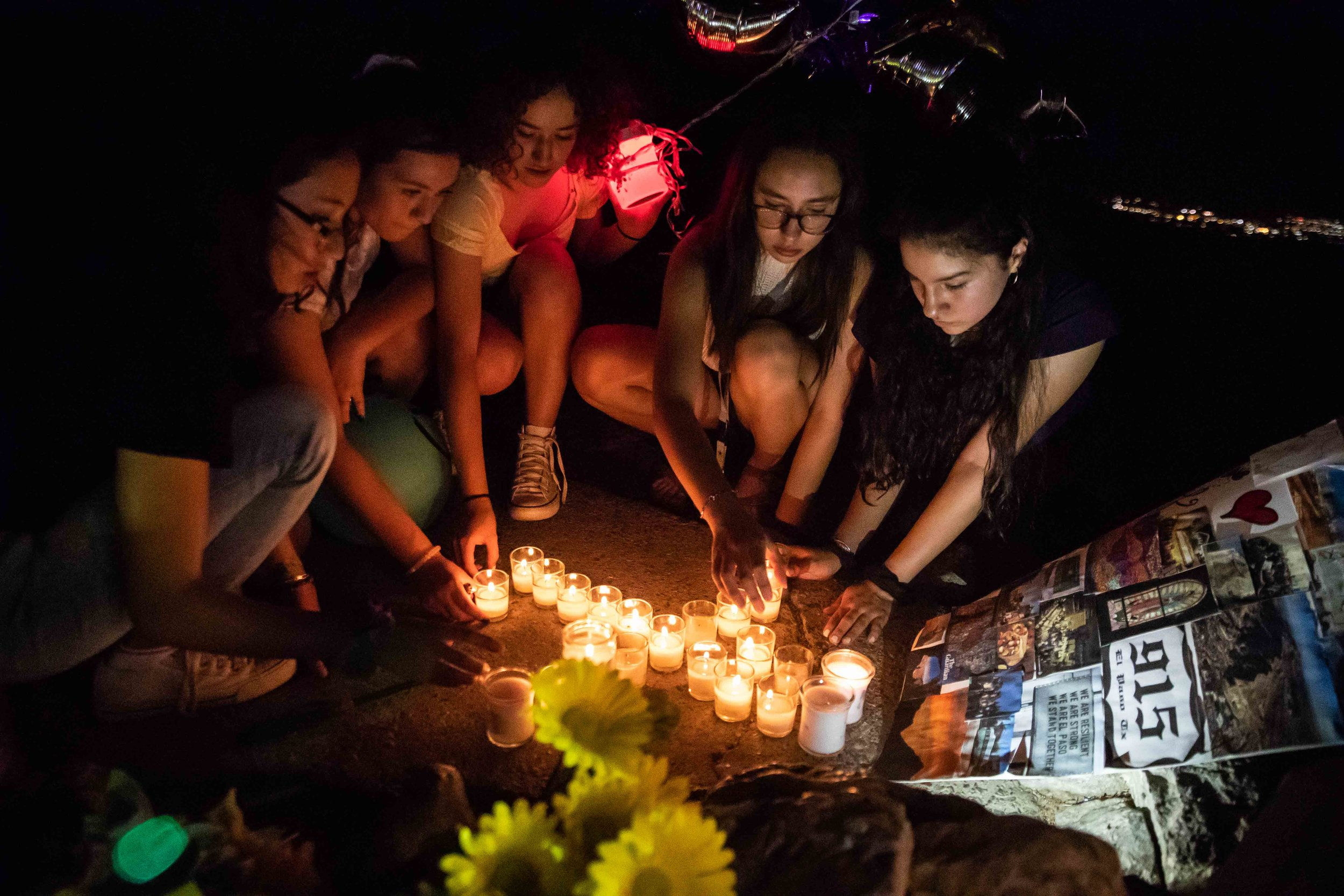 From left, Amanda Torres, Andrea Carrasco, Alexa Carrasco, Chloe Trujillo and Britney Martinez light candles at the Scenic Drive - Overlook to honor the victims of the mass shooting occurred in Walmart last Saturday monirng in El Paso on Monday, August 5, 2019.