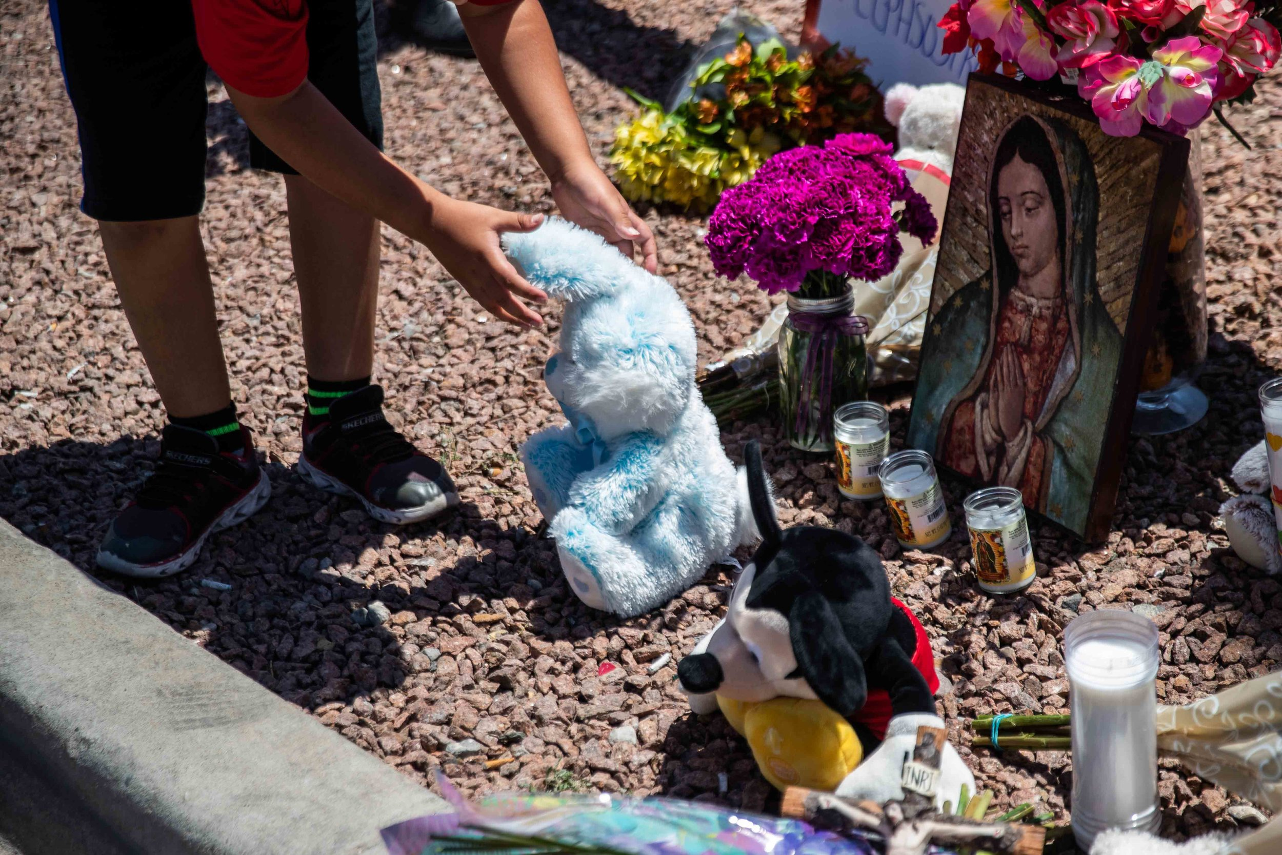 Kevin Roldan leaves a stuffed animal next to a Virgen de Guadalupe poster to honor the memory of the victims of the mass shooting occurred in Walmart on Saturday morning in El Paso on Sunday, August 4, 2019.