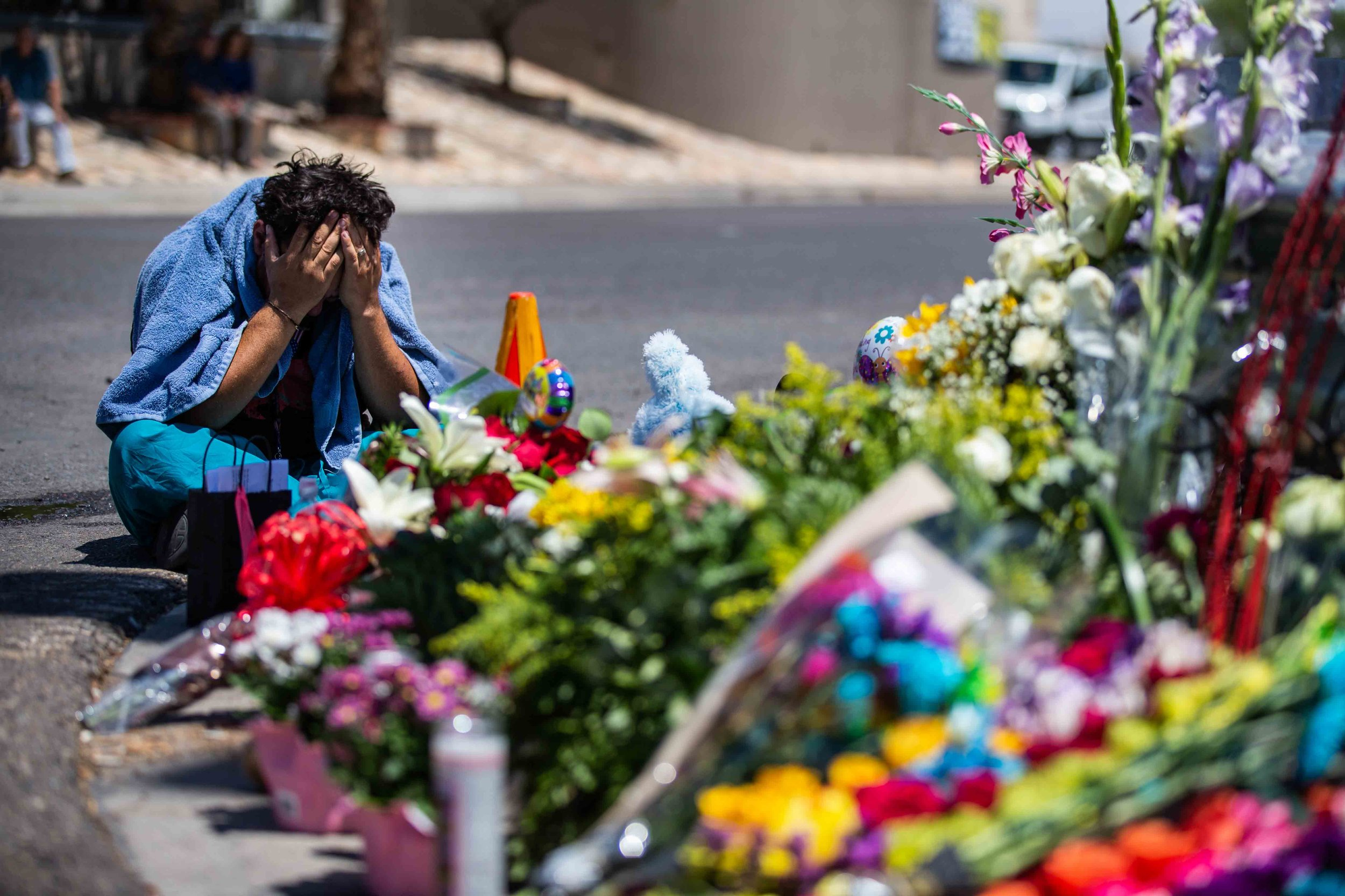 Felipe Avila puts his head in his hands as he cries at the place where the locals bring flowers, stuffed animals, candels and posters to honor the memory of the victims of the mass shooting occurred in Walmart on Saturday morning in El Paso on Sunday, August 4, 2019.